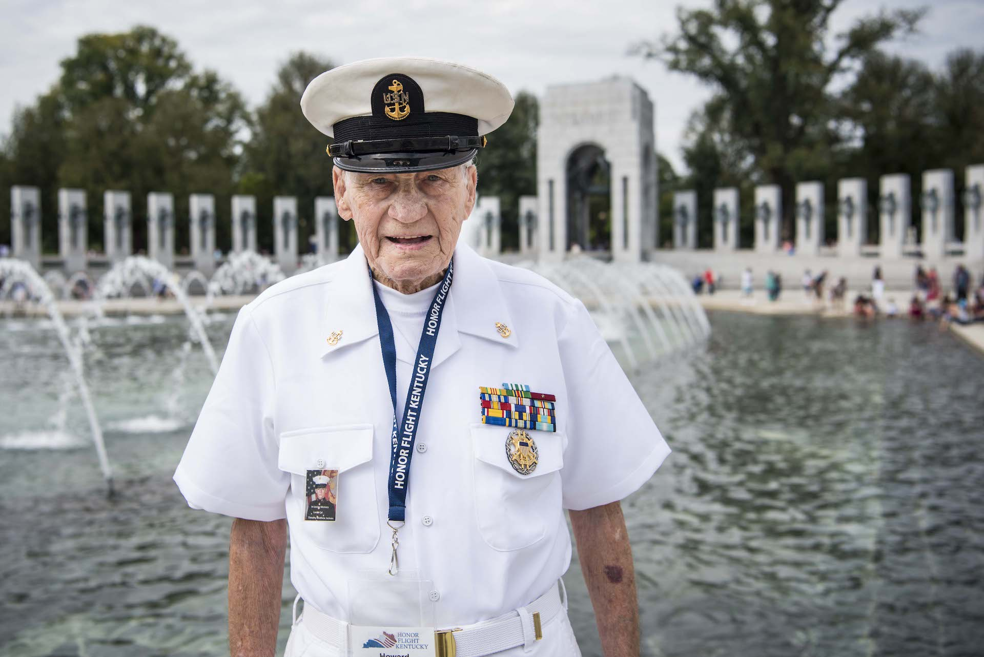 Howard smiles for a photo in his white Navy uniform in front of the World War II memorial fountain.