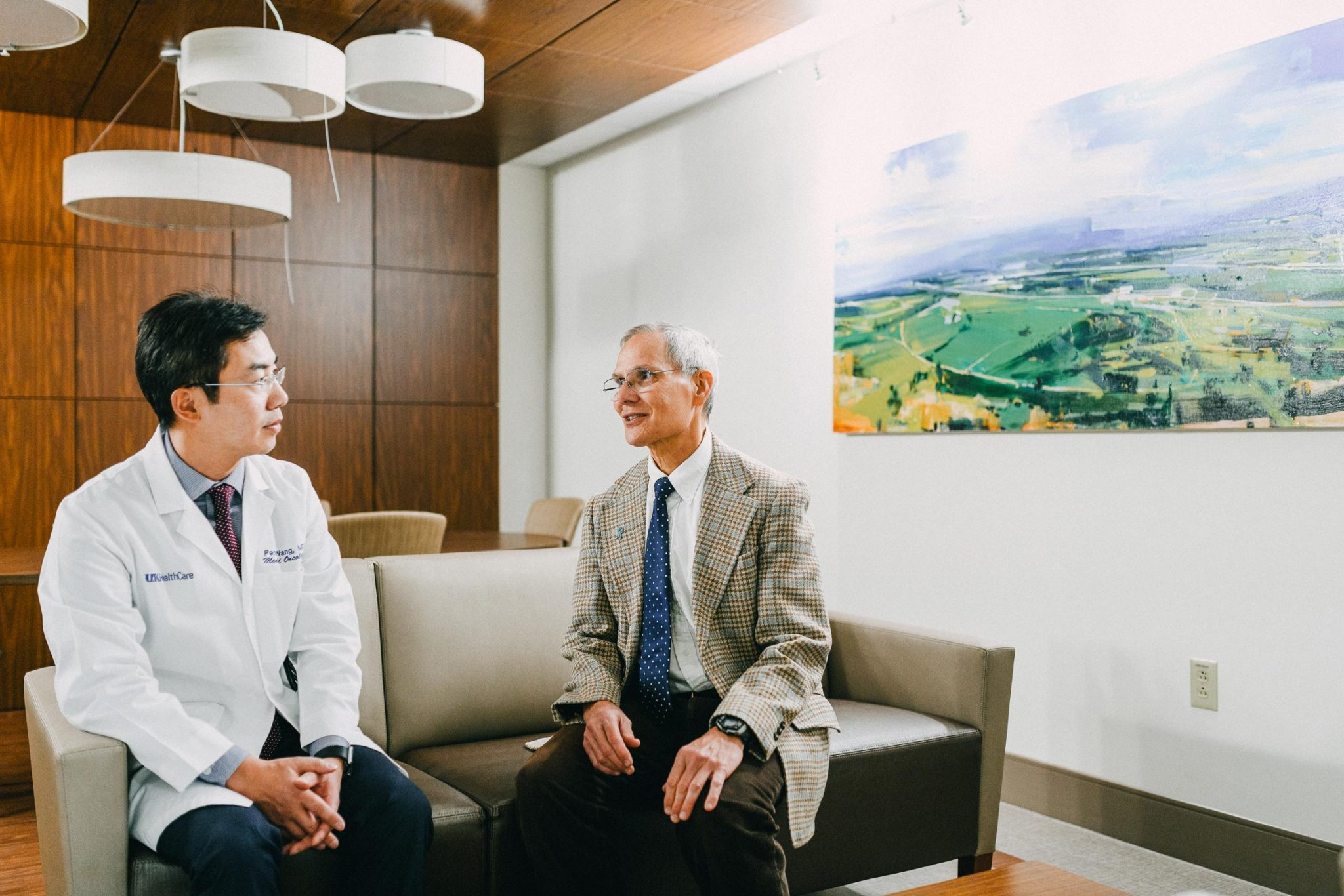 Dr. Charles Lutz seated on a bench having a conversation with Dr. Peng Wang.