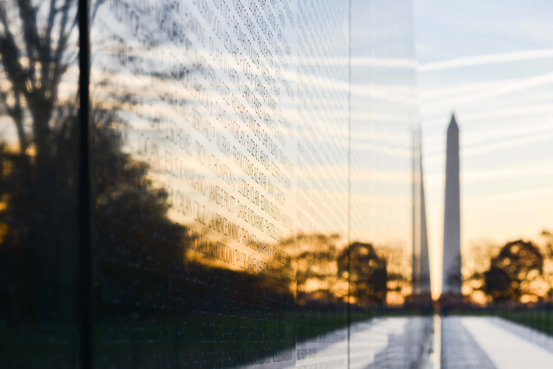 Close up of the names inscribed on the Vietnam Veterans Memorial wall and the Washington Monument in the distance.