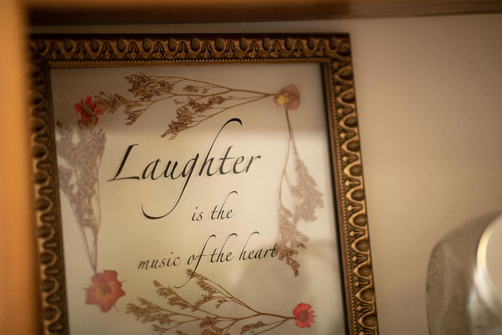 A framed quote that reads Laughter is the Music of the Heart