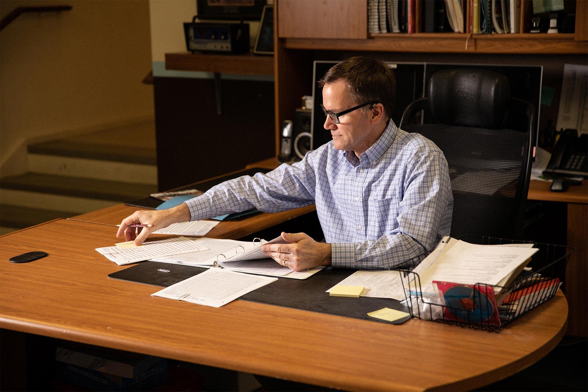 Bill Crawford sitting at a desk, examining paperwork
