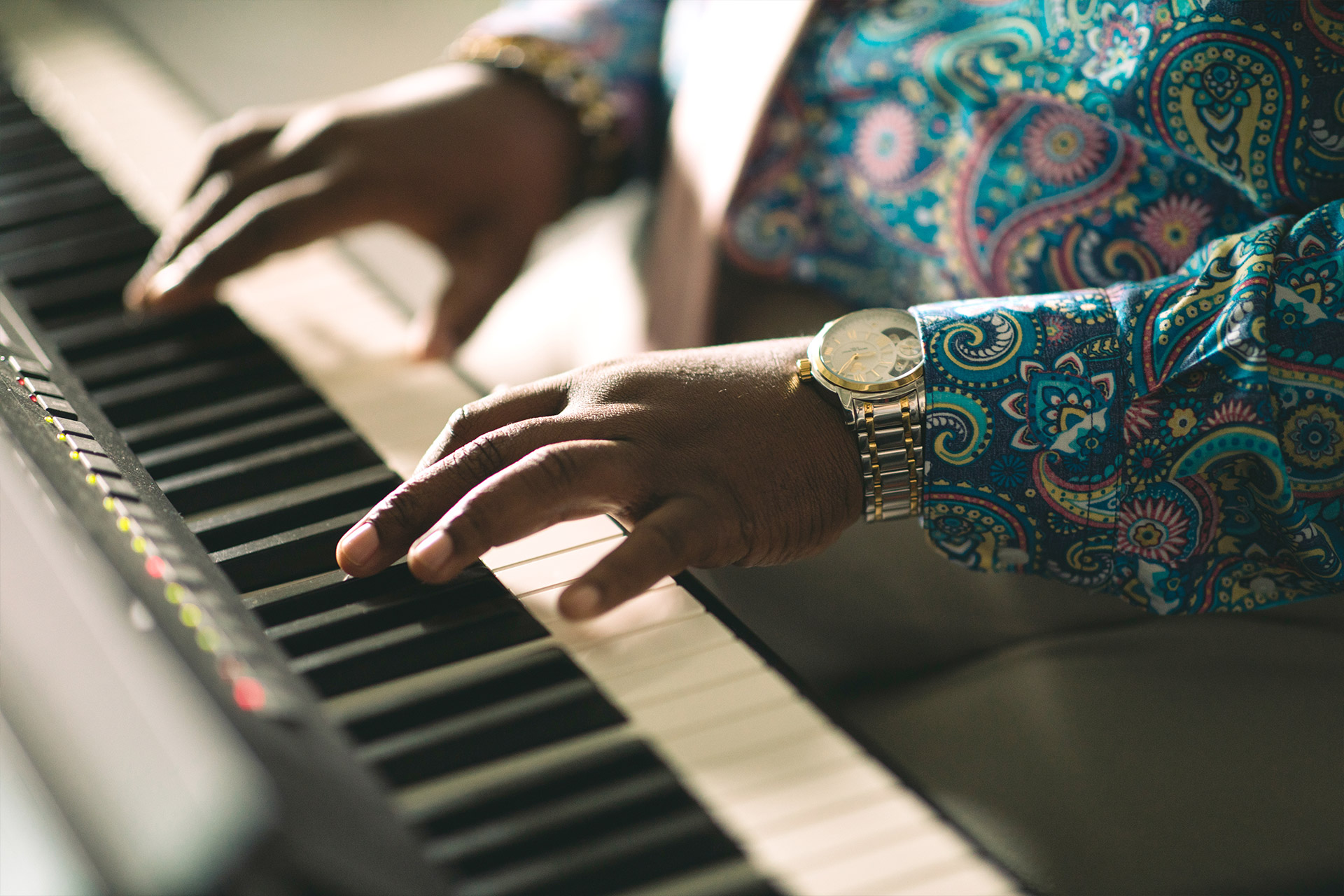 Close up of Damon's hands playing a keyboard for his class.