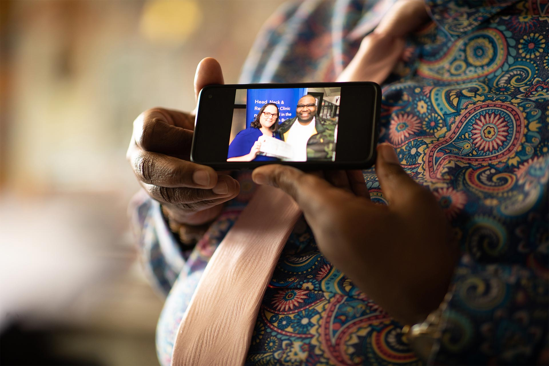 Damon Greene holding a cell phone showing an image of himself and a UK healthcare professional