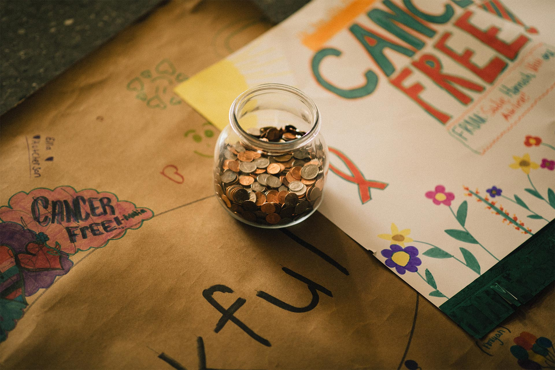 A glass jar full of coins and hand drawn posters
