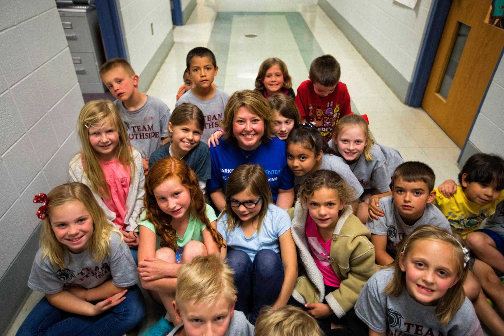 Erika Carter sitting in a school hallway surrounded by her students