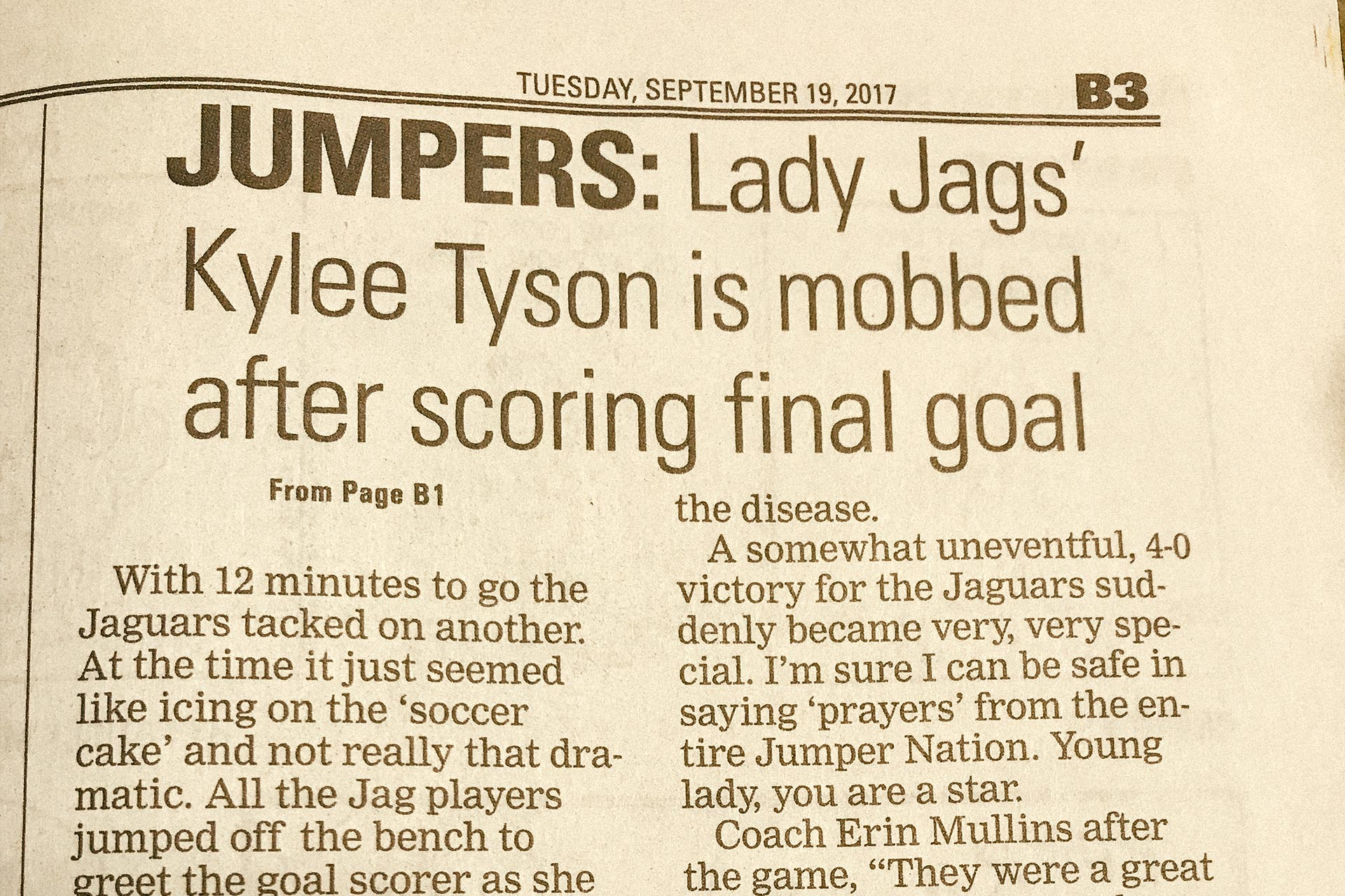 Newspaper headline reads: 'Lady Jags' Kylee Tyson is mobbed after scoring final goal.'