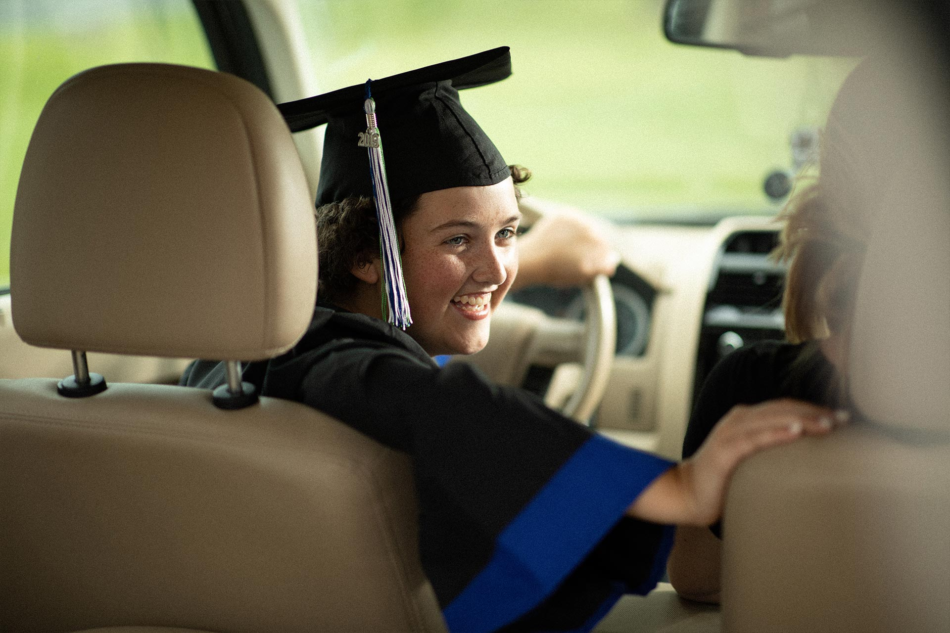 Kylee Tyson sitting in the driver's seat of a car, wearing her graduation cap and gown.