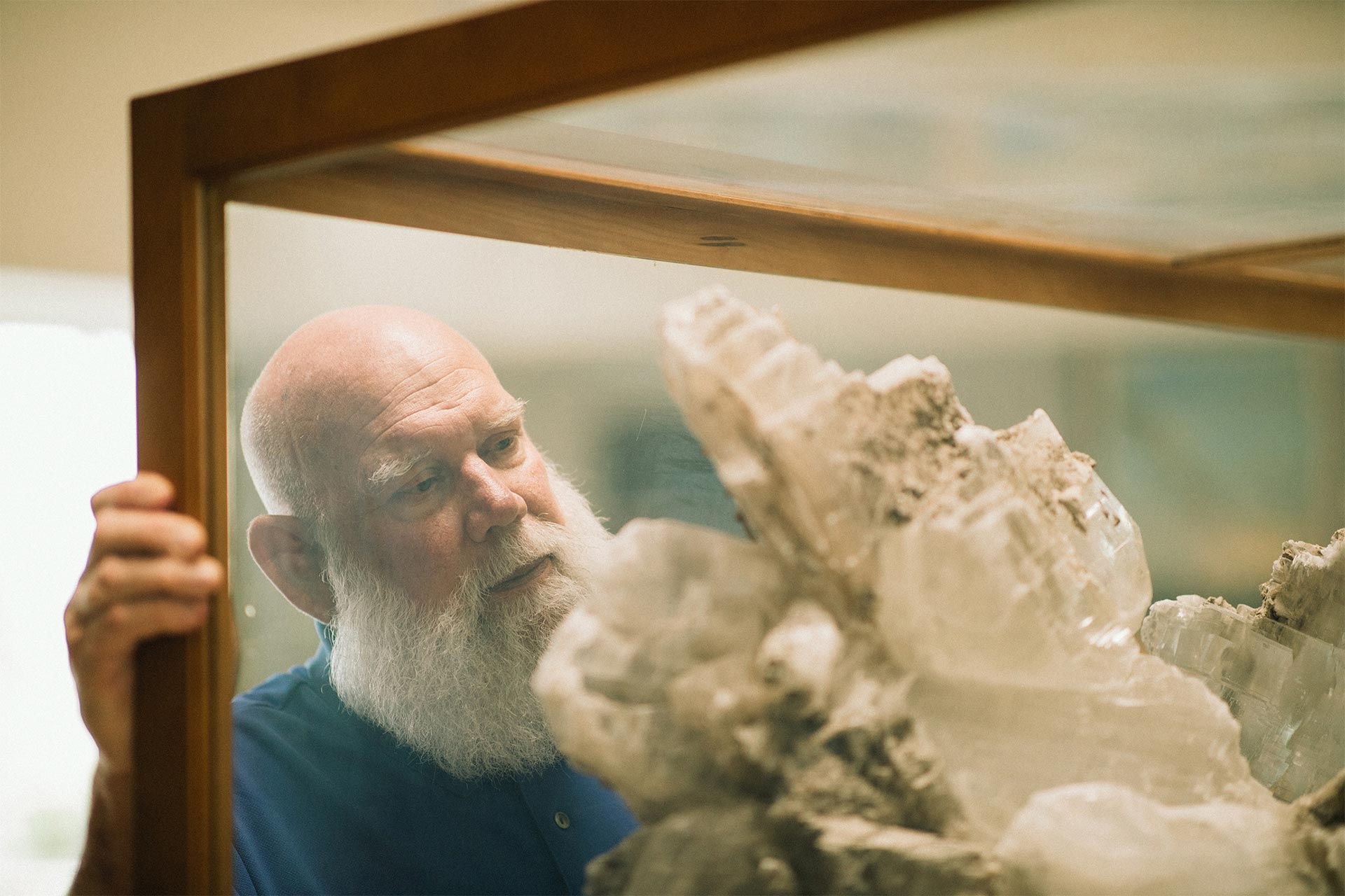 Patrick Gooding examining rock formation in display case