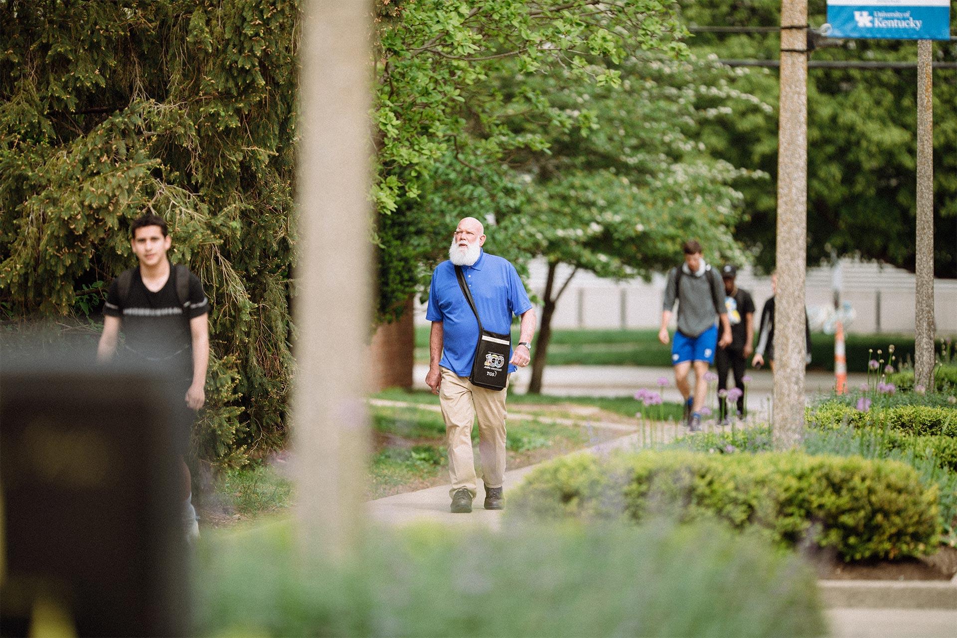 Patrick Gooding walking down sidewalk carrying a black bag