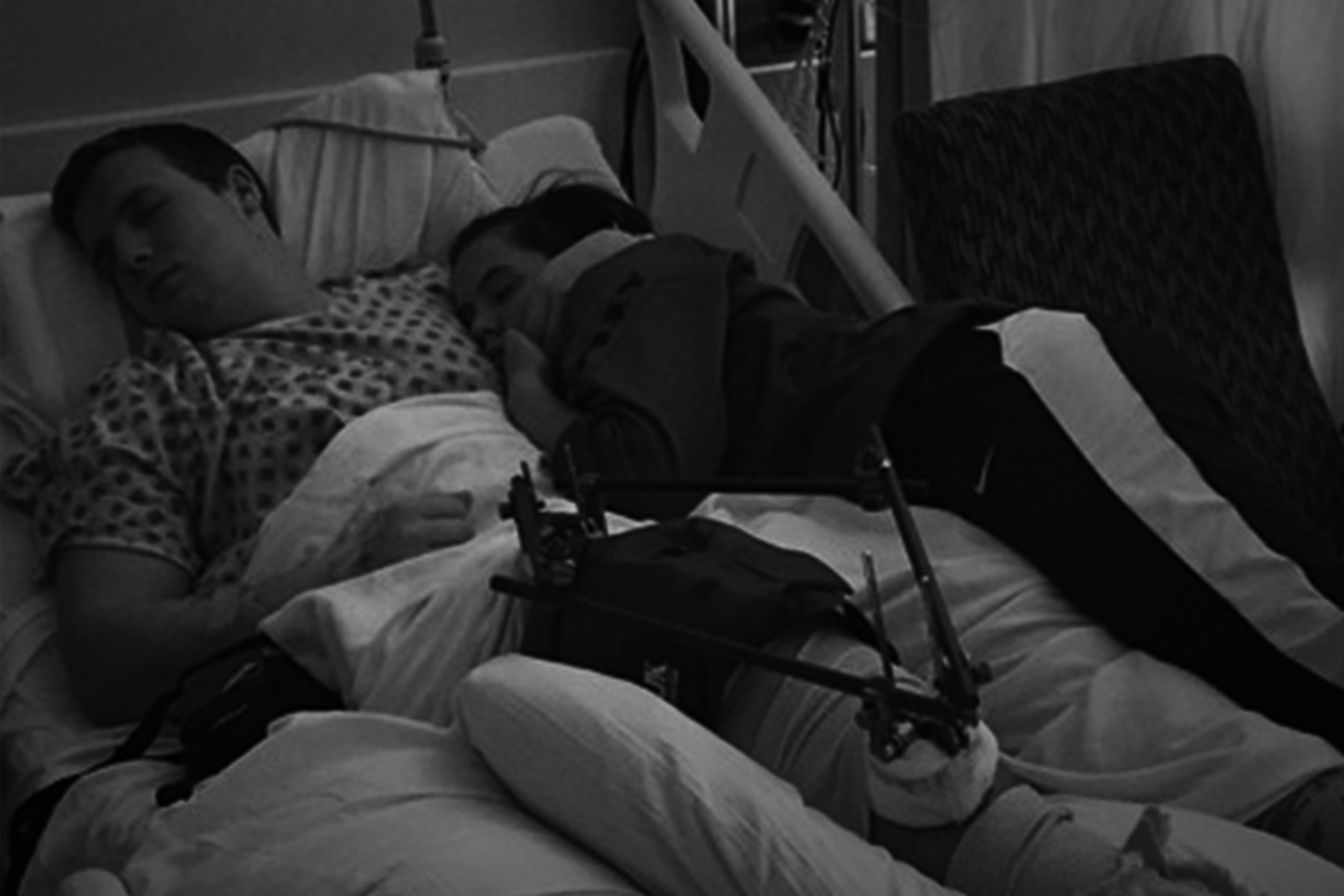 Black and white photo of Caleb and Amelia sleeping in his hospital bed. Caleb's knee has an external fixator attached to stabilize it.