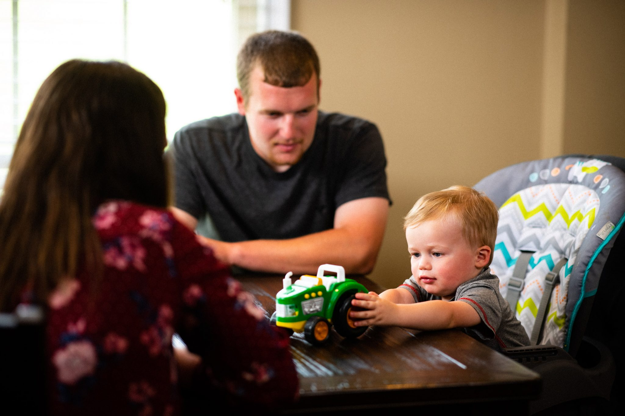 Caleb and Amelia watch Cason play with a toy tractor at their dining room table.