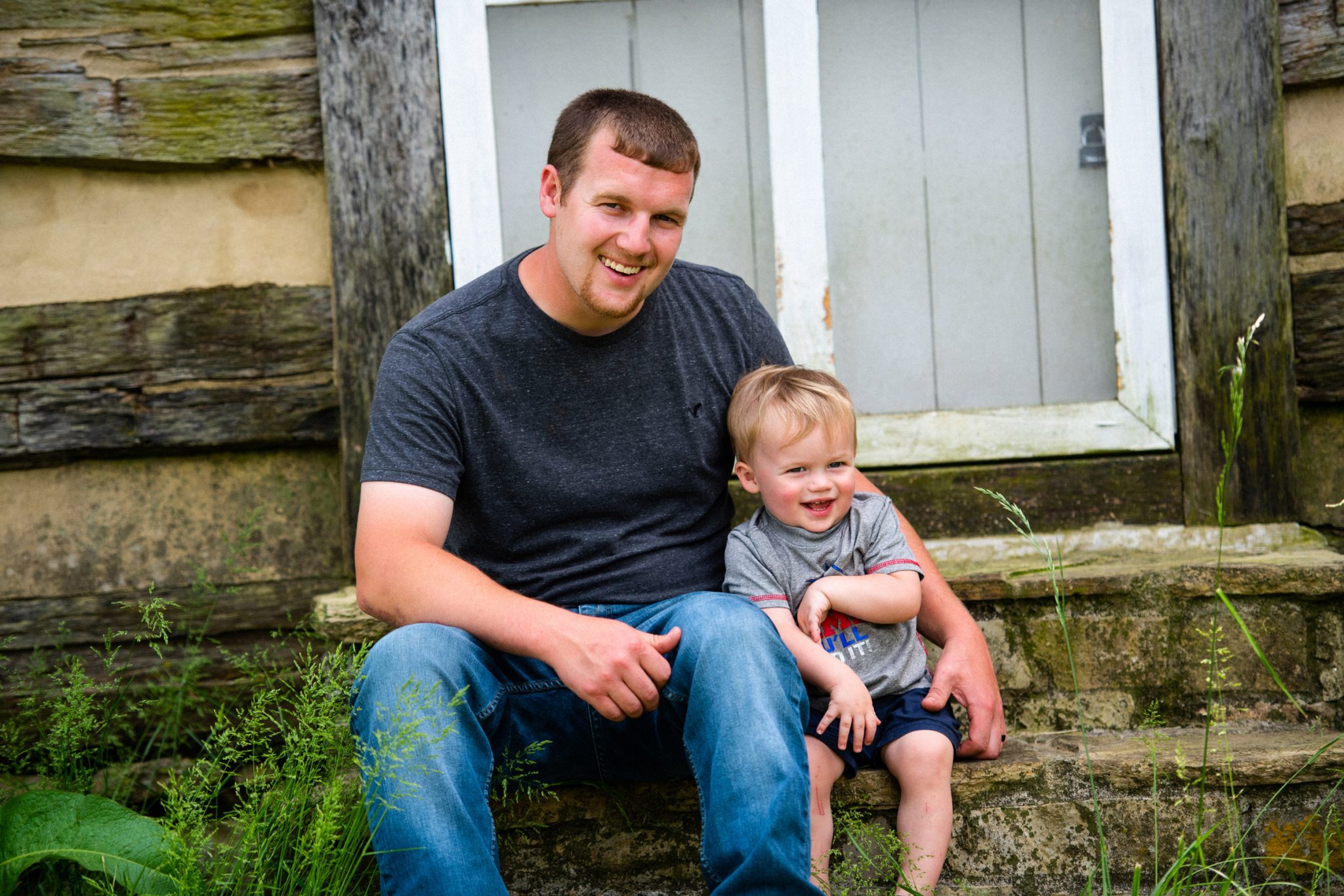Caleb and his young song Cason sit and smile together on some steps for a photo outside.