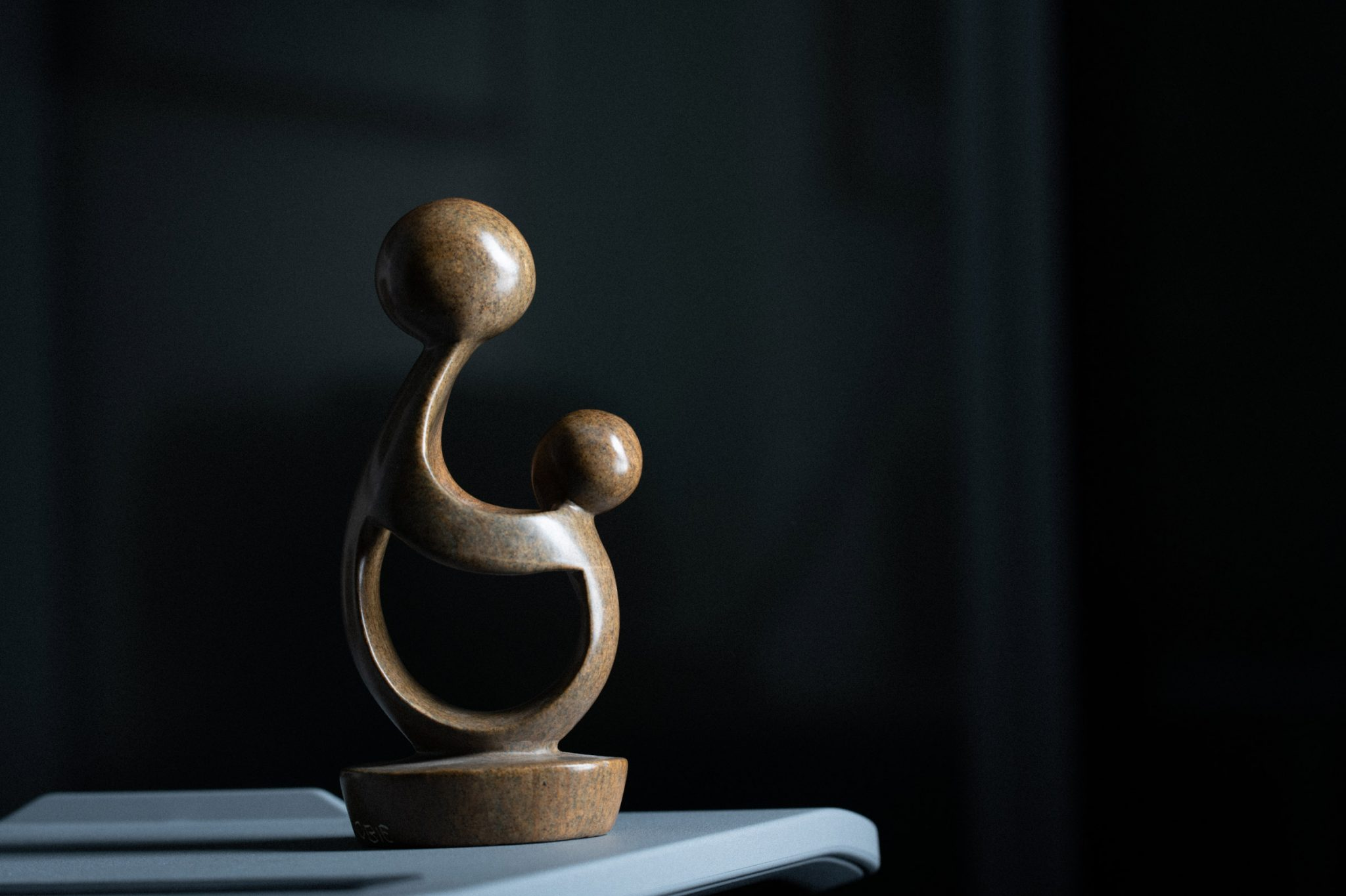 Chris's DAISY Award for Extraordinary Nursing, awarded in 2017. A brown, curving, abstract sculpture of two figures that might be interpreted as one large figure helping a smaller figure.