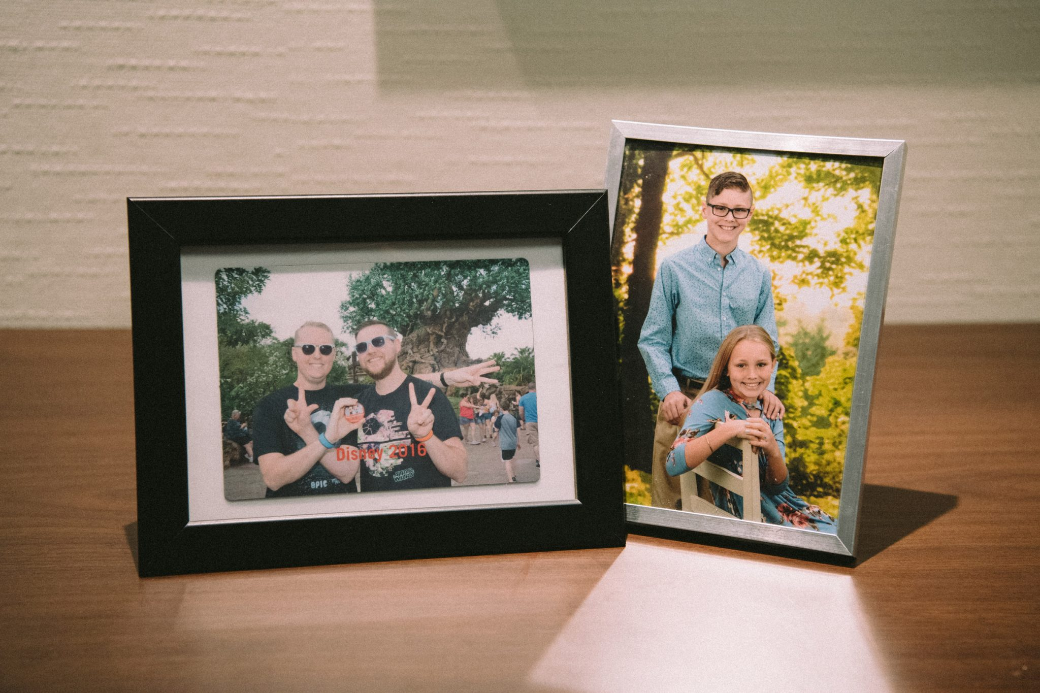 A framed photo of Chris and his husband in front of Disney's Animal Kingdom Tree of Life, and a second framed photo of his two teenaged kids.