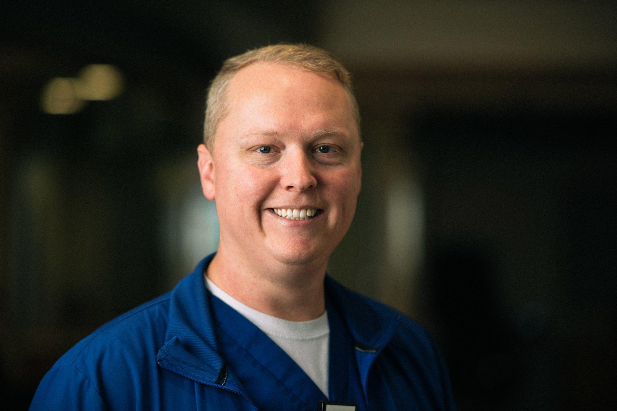 Chris smiles brightly while wearing his blue nursing scrubs.
