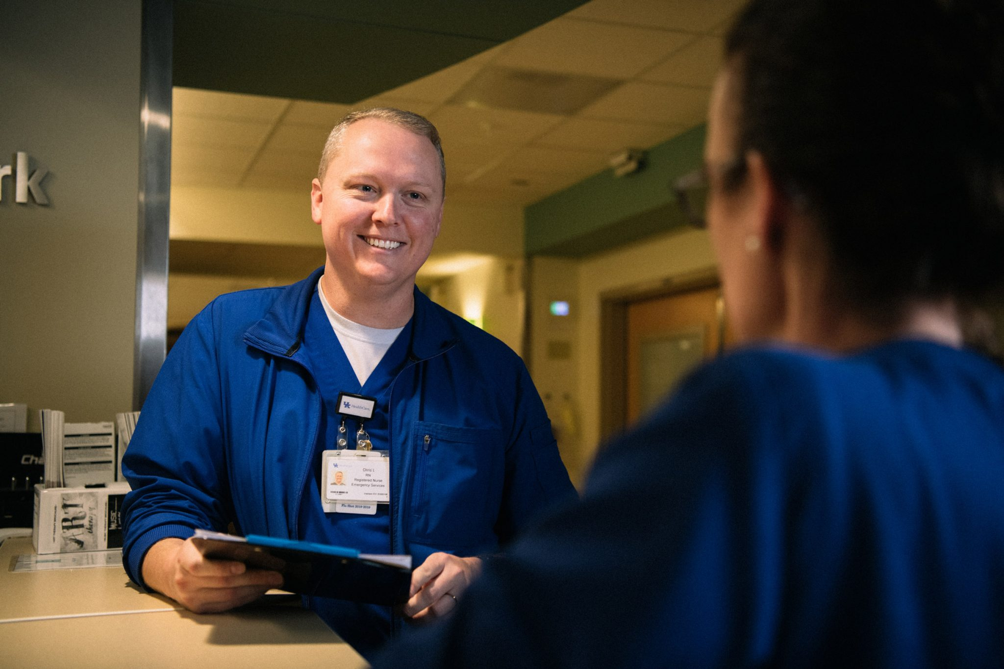 Chris smiles while holding a clipboard and listening to another nurse talk to him.