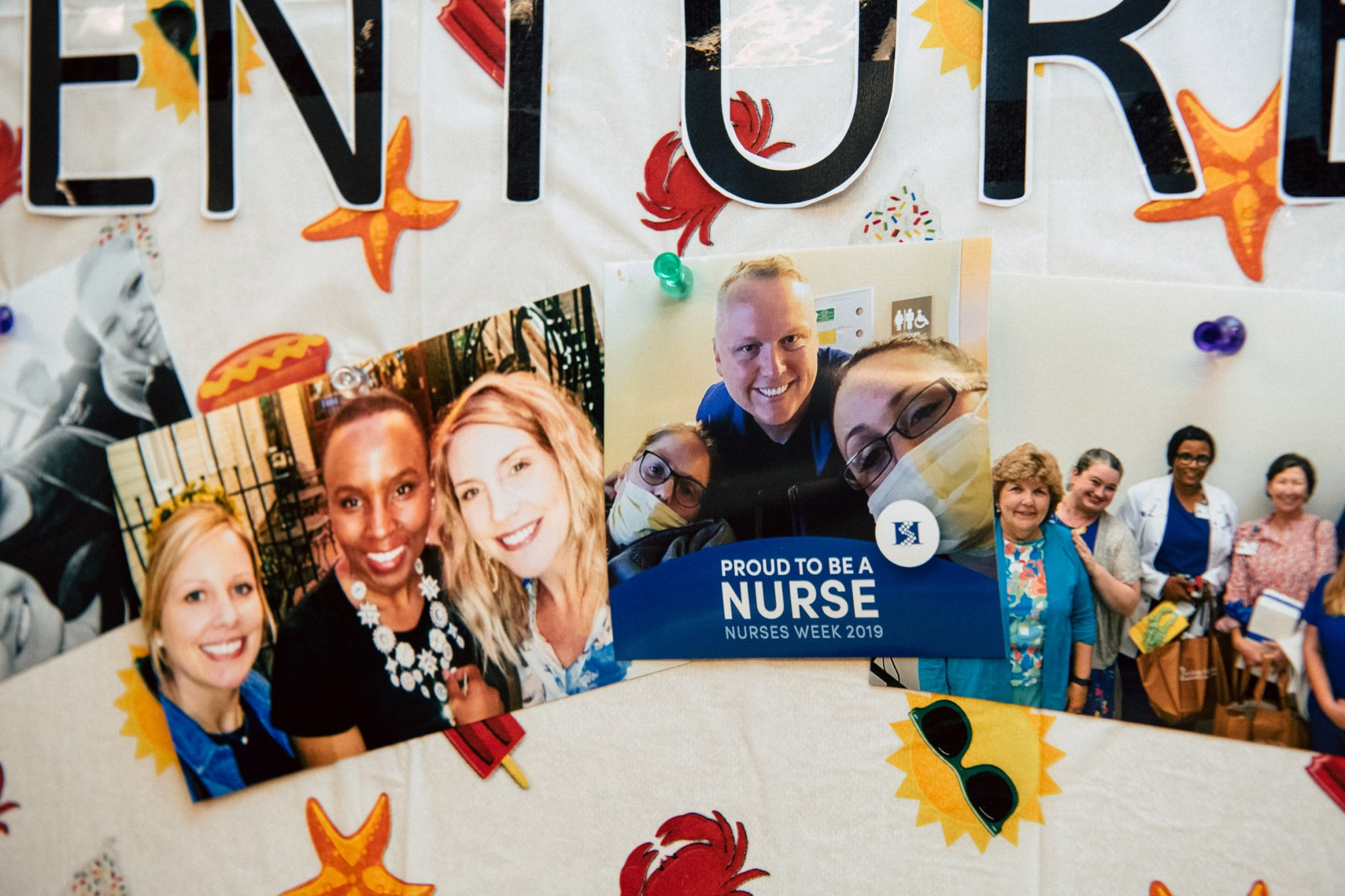 """Photos pinned to a decorated cork board. One is of Chris with two other nurses with a """"Proud to be a nurse. Nurses week 2019"""" graphic printed on it."""