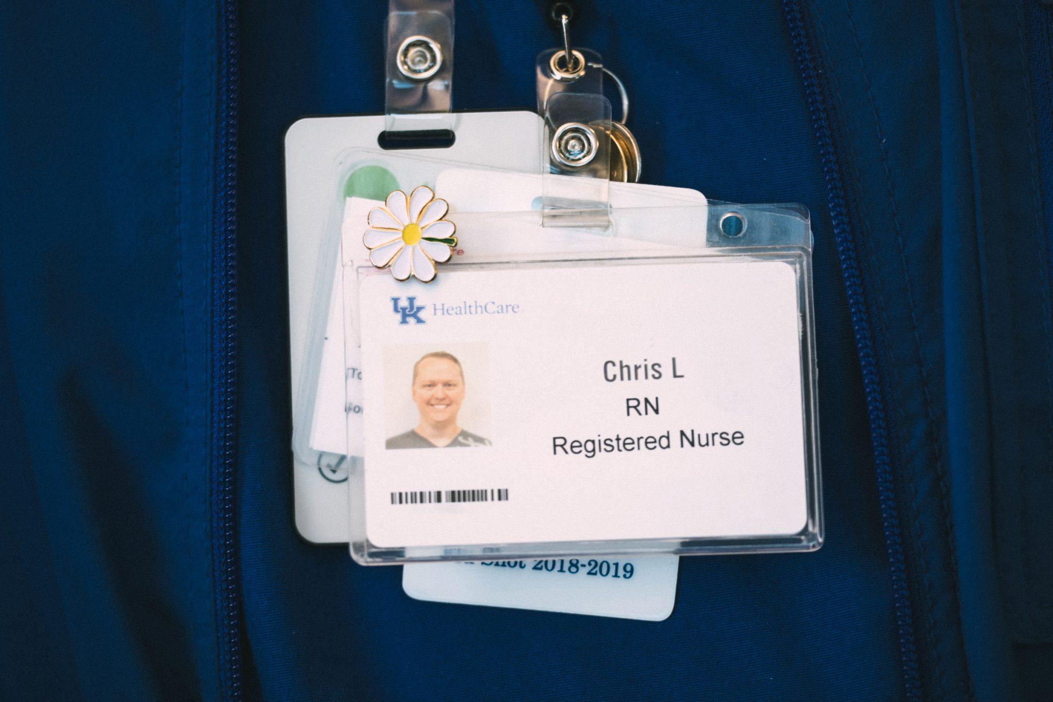 A close up of Chris's RN ID badges and DAISY award pin.