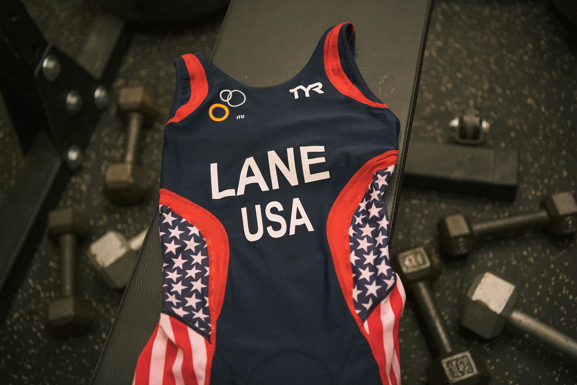 """Patty's running leotard with her last name """"LANE"""" above """"USA"""". The leotard is navy blue with red stripes and decorated with the American flag on the sides."""