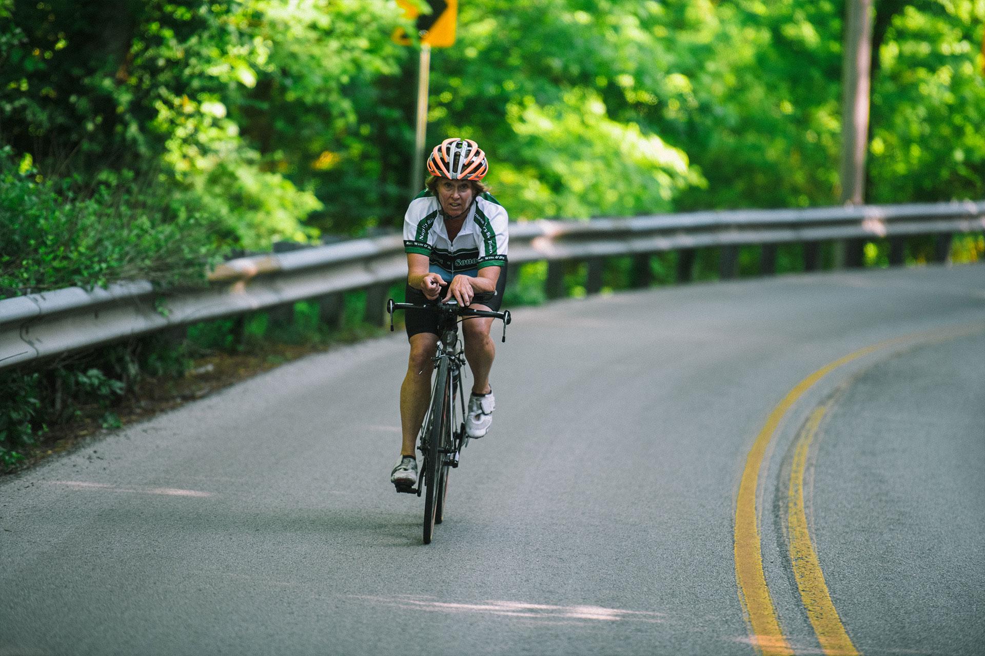 Patty bikes down a road outside.