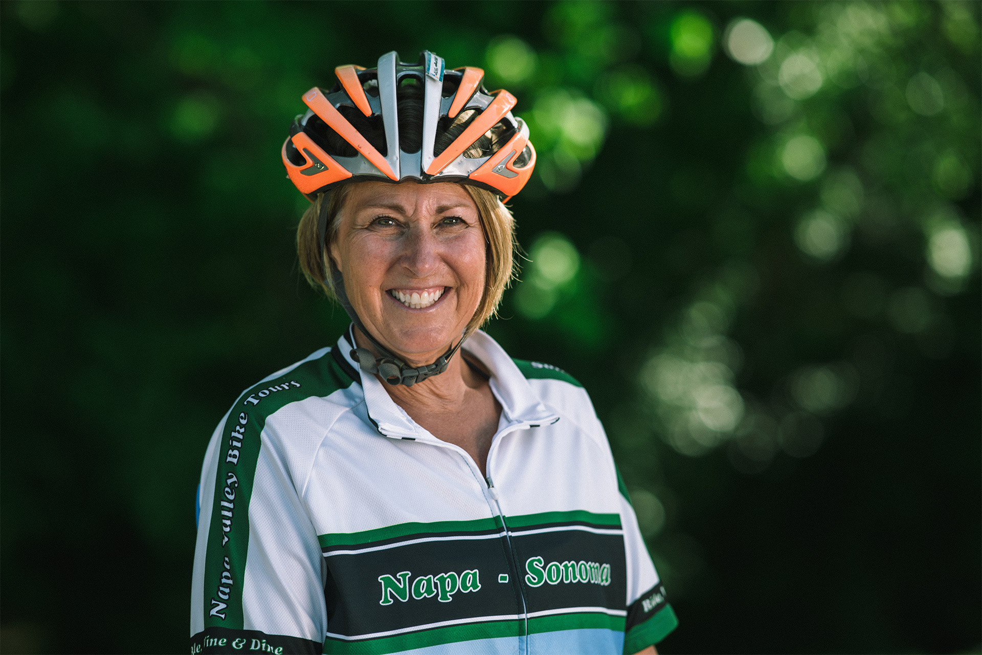 Patty smiles brightly for a photo while wearing an orange and silver biking helmet and white and green cycling kit.