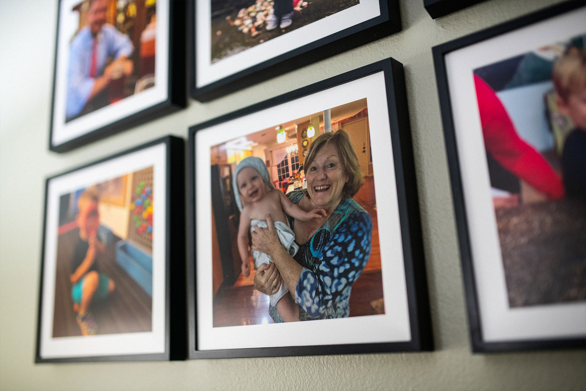 Framed photographs of Suzanne and her grandkids hanging on a wall.