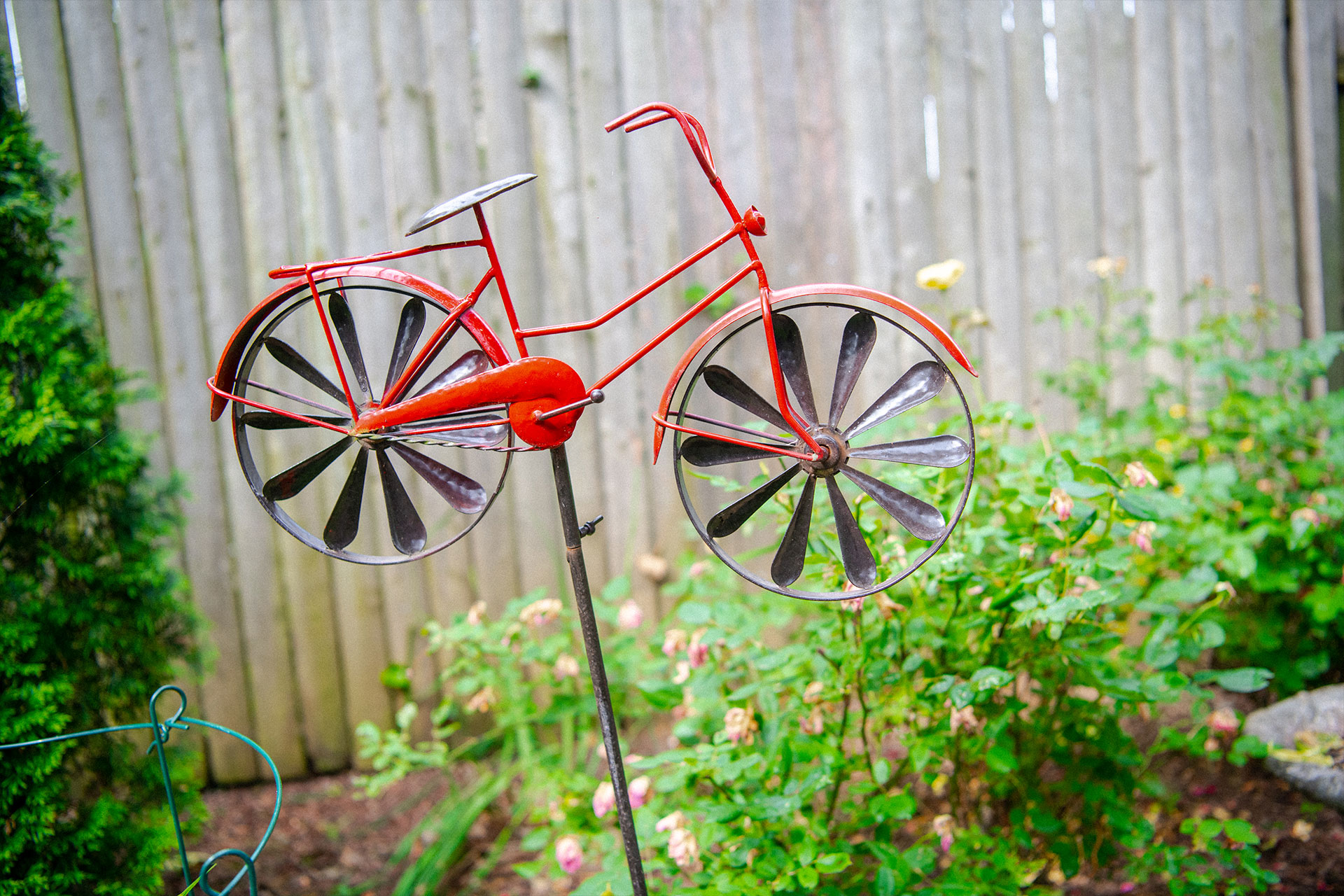 A red bicycle garden ornament. The wheels are wind spinners.