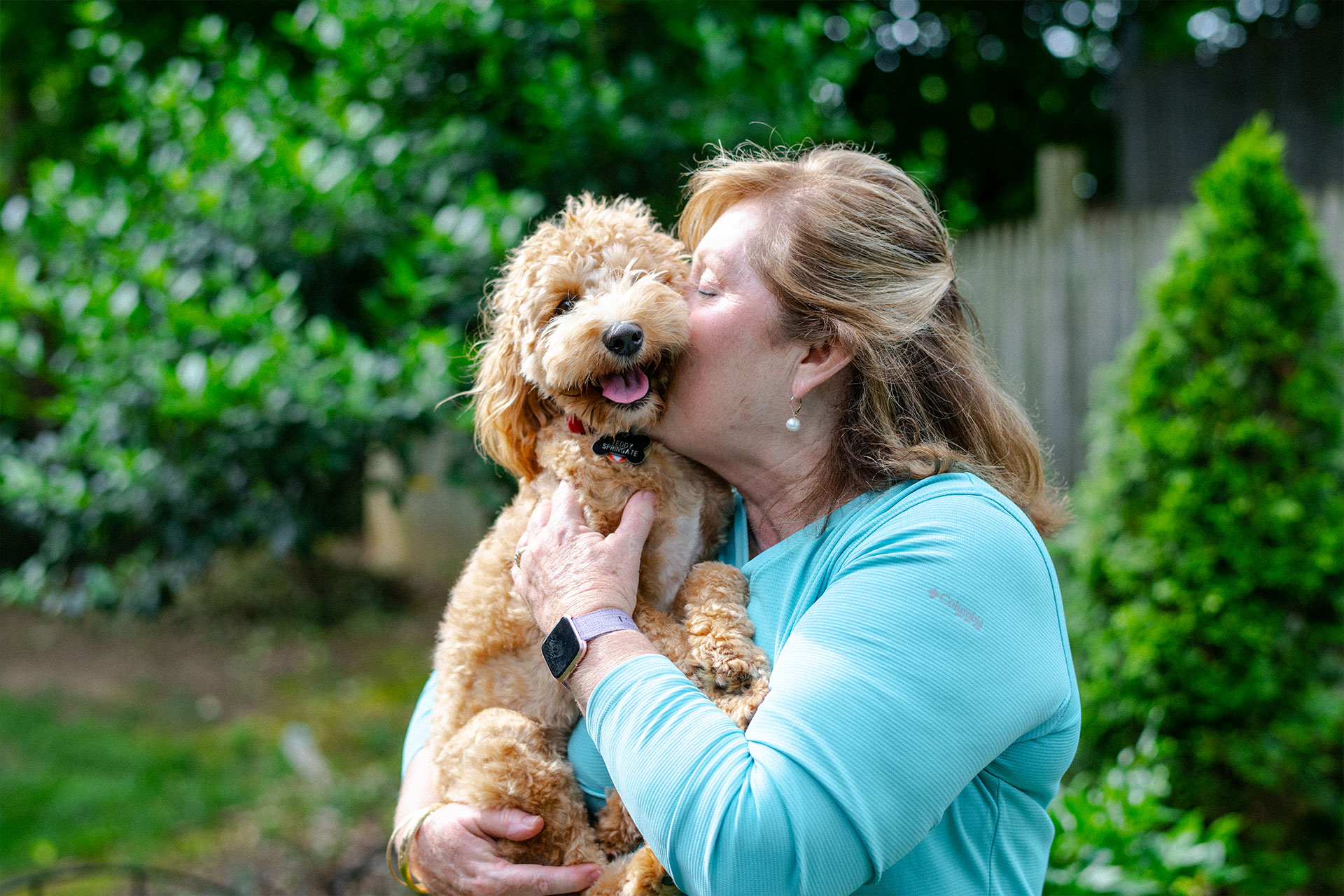 Suzanne holds and kisses her happy dog, Teddy.