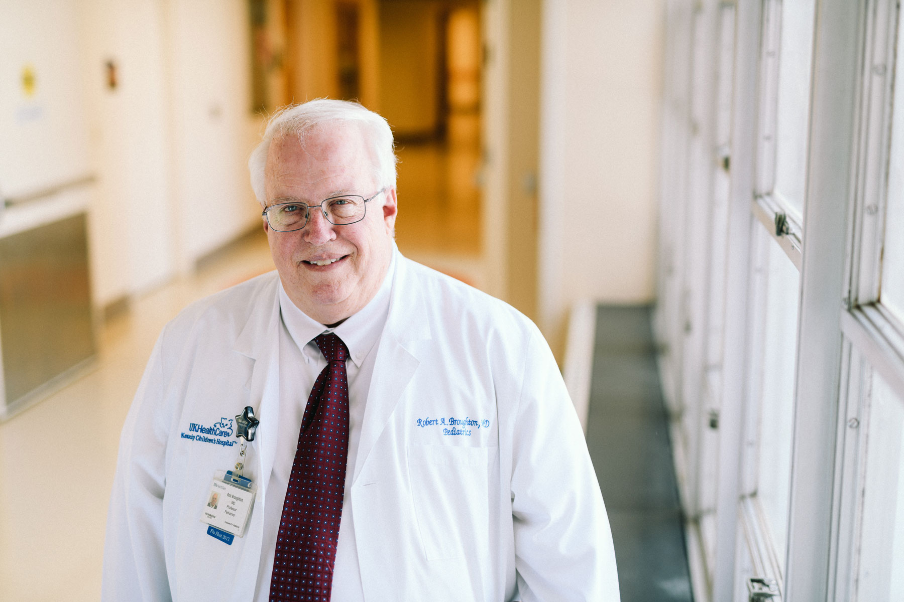 Dr. Broughton wears his white doctor's coat and smiles for a photo in a hallway at UK HealthCare.