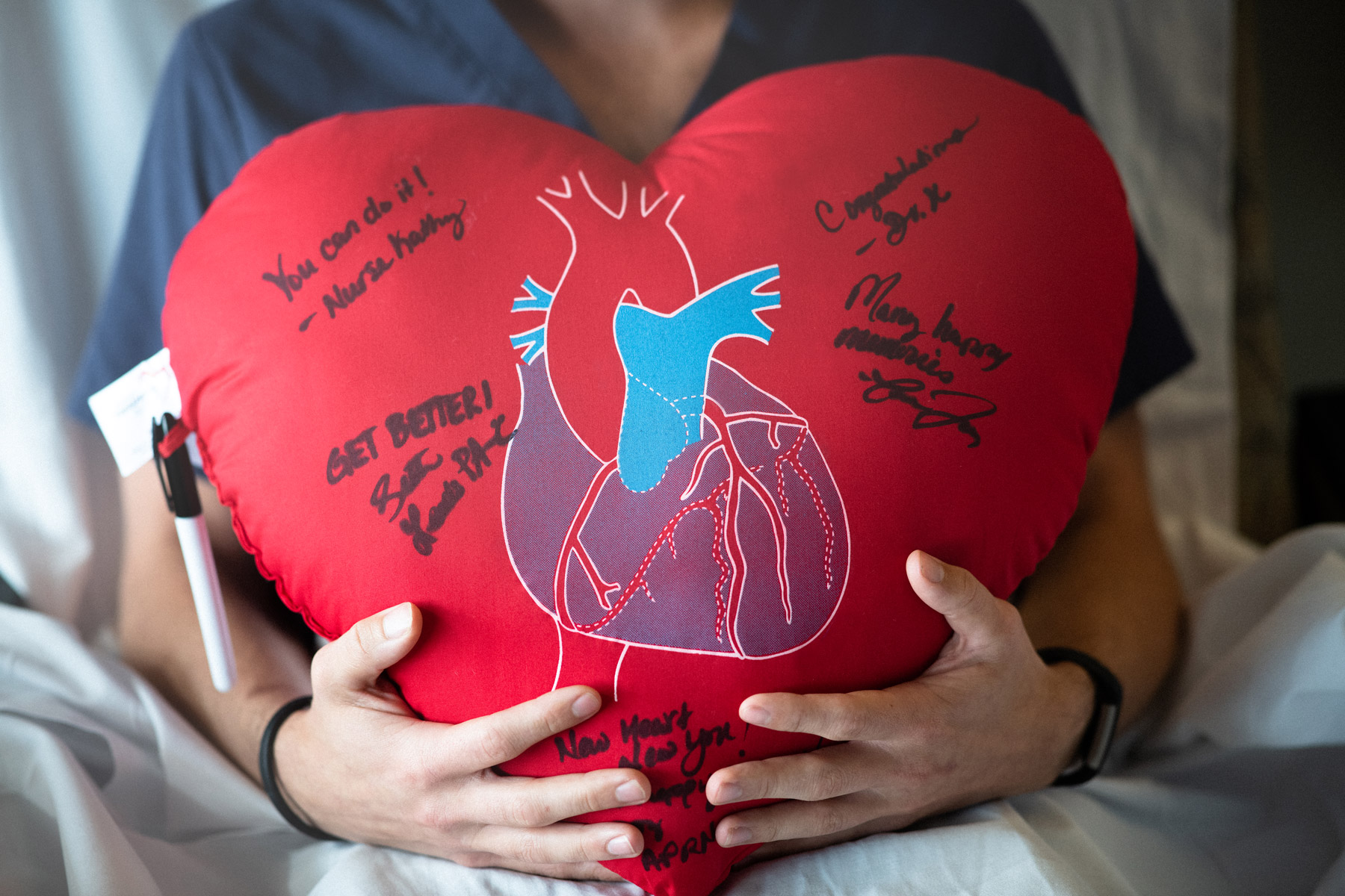 A large, red, plush heart with an anatomical heart printed in the front is signed in sharpie by members of the patient's care team at the hospital.