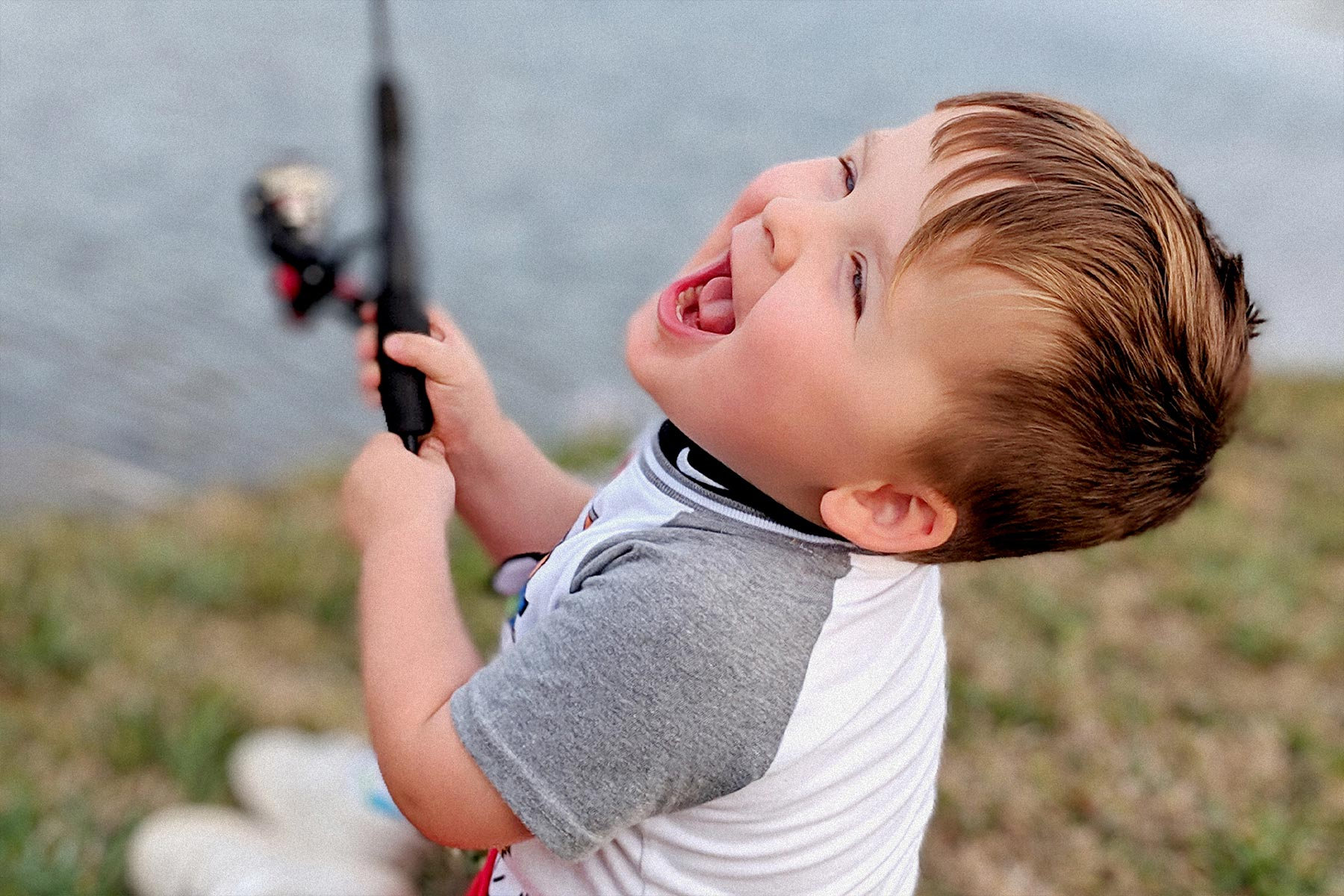 Kase laughs gleefully while holding a fishing pole.
