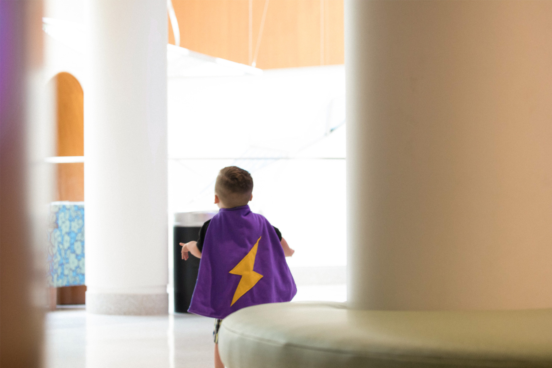 Kase is walking away wearing a purple cape decorated with a large yellow lightning bolt on his back.