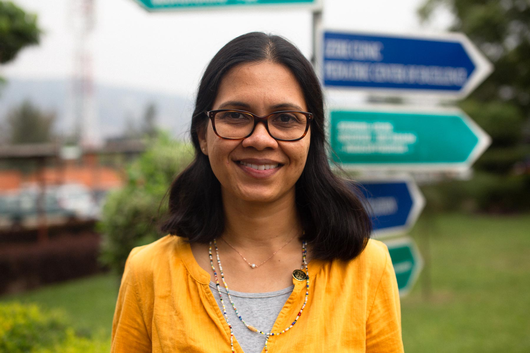 Dr. Shenoi smiles in front of a signpost outside.