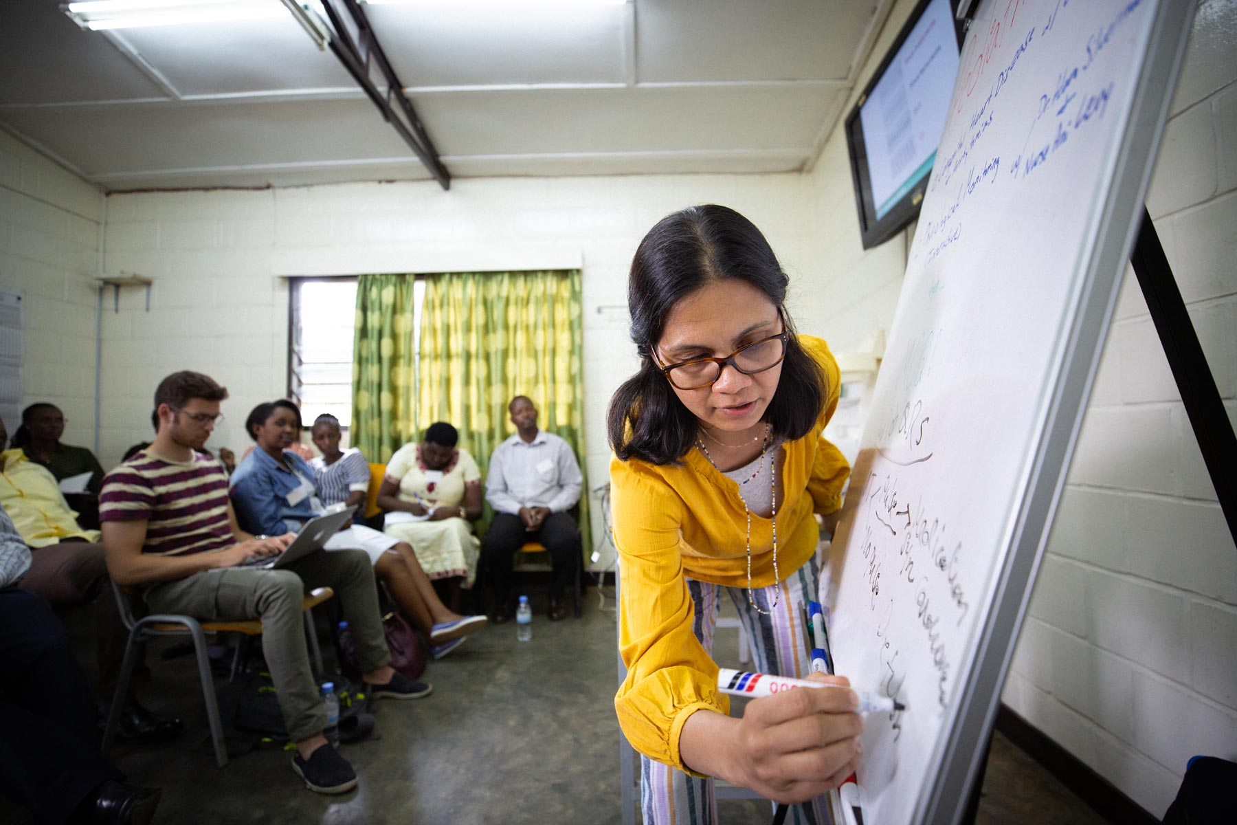 Dr. Shenoi writes on a whiteboard while training with doctors and nurses in Rwanda.
