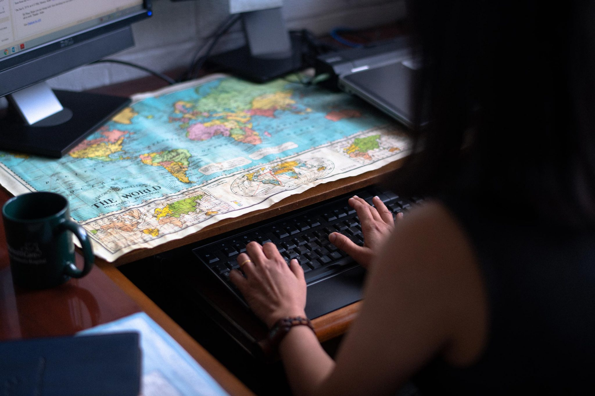Dr. Shenoi types on her computer with a world map on her desk in front of her.