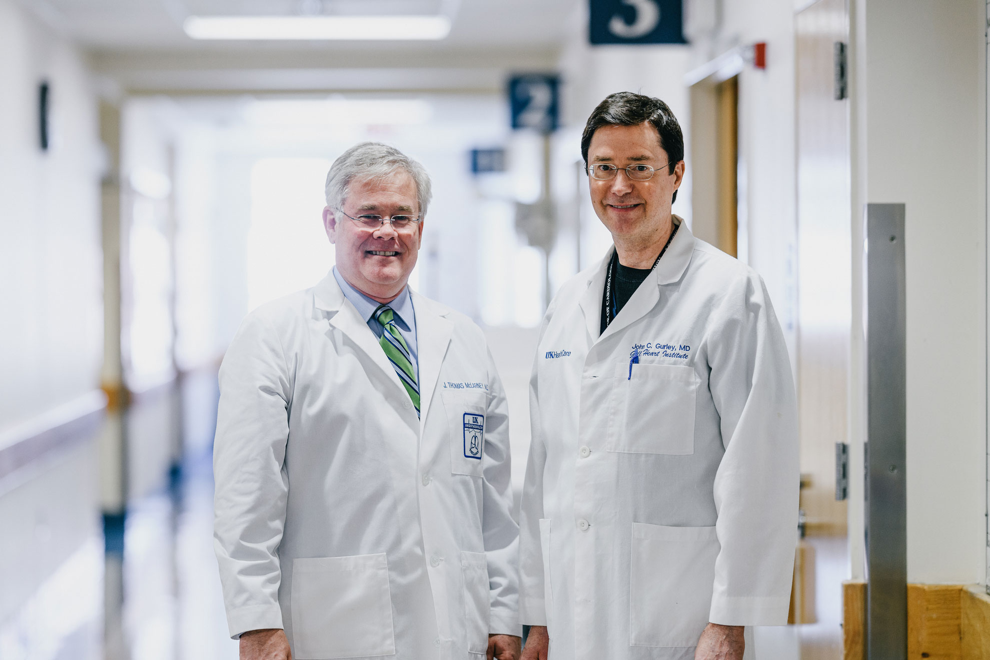 Dr. McLarney and Dr. Gurley wearing their white doctor's coats smile for a photo in a hallway at the hospital.