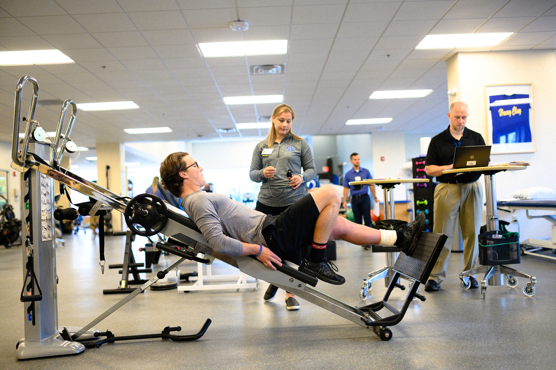 Peter performs his physical therapy exercises while one of his therapists watches.