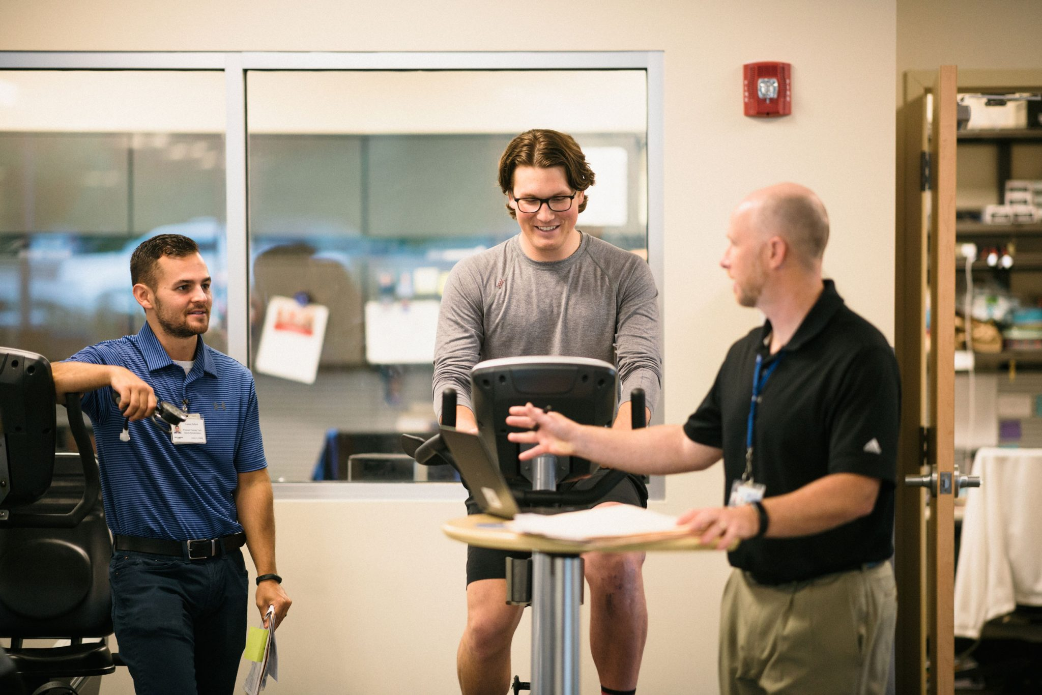 Peter's physical therapists talk while he rides a stationary bike.