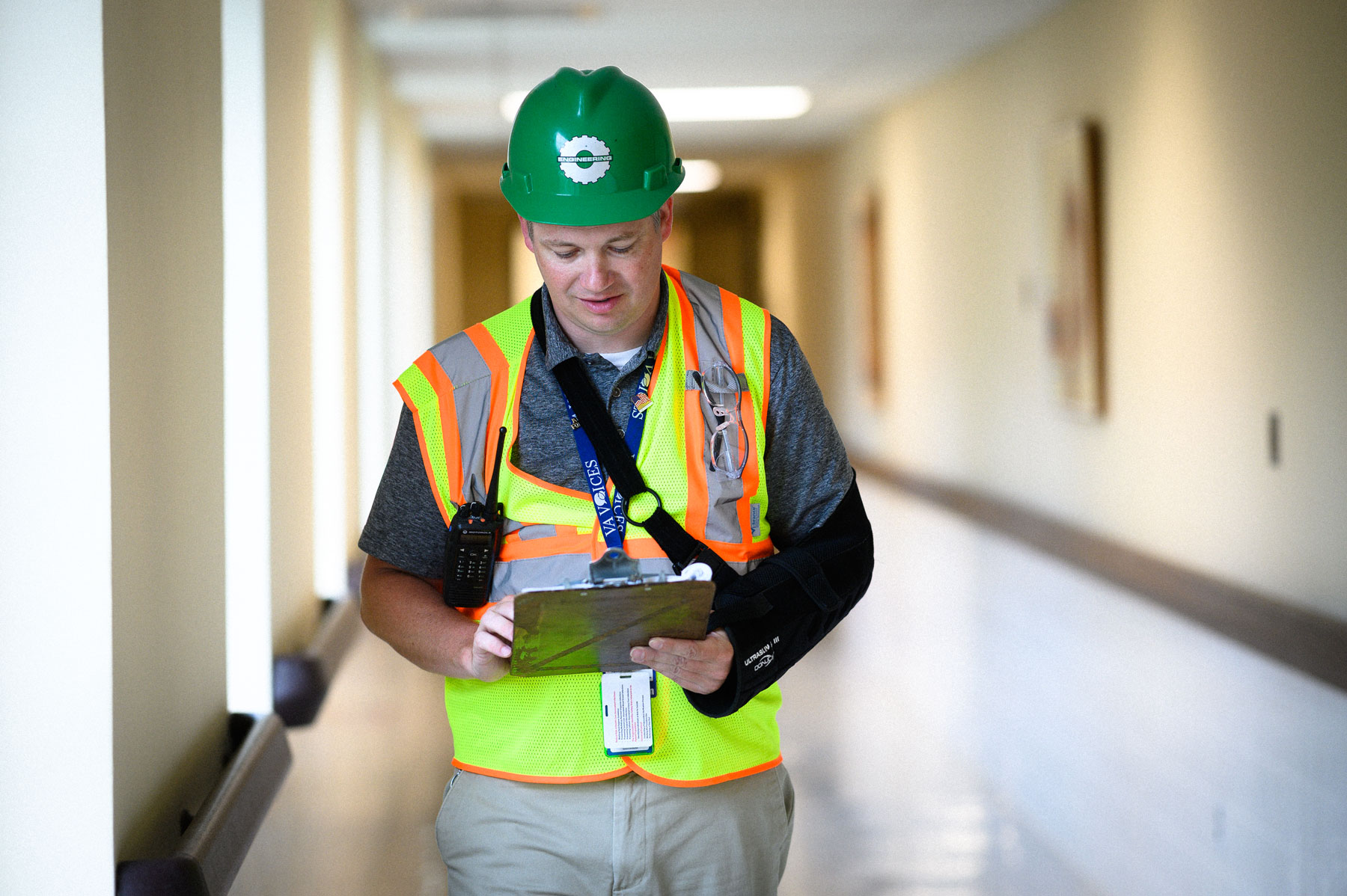 Leonard walks down a hall with a clipboard while wearing a safety vest and construction helmet.