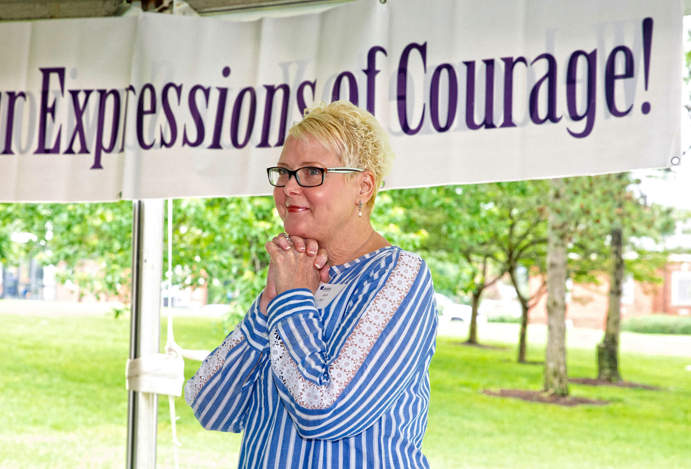 Sarah clasps her hands under her chin and smiles at the Expressions of Courage event.