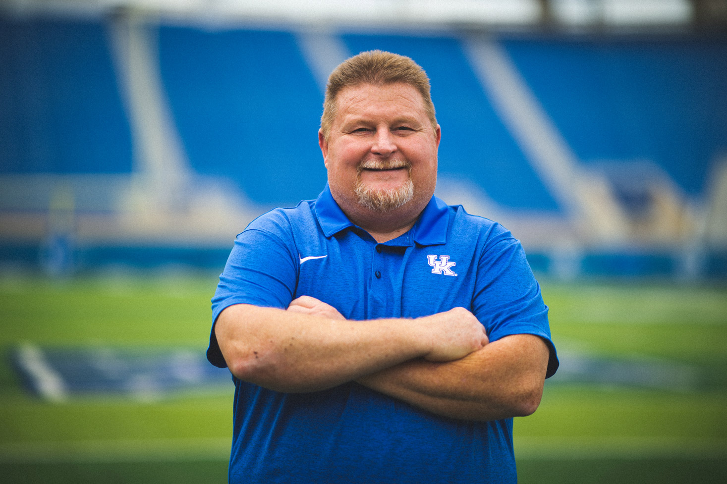 Jimmy crosses his arms and smiles while out on the UK Football field.
