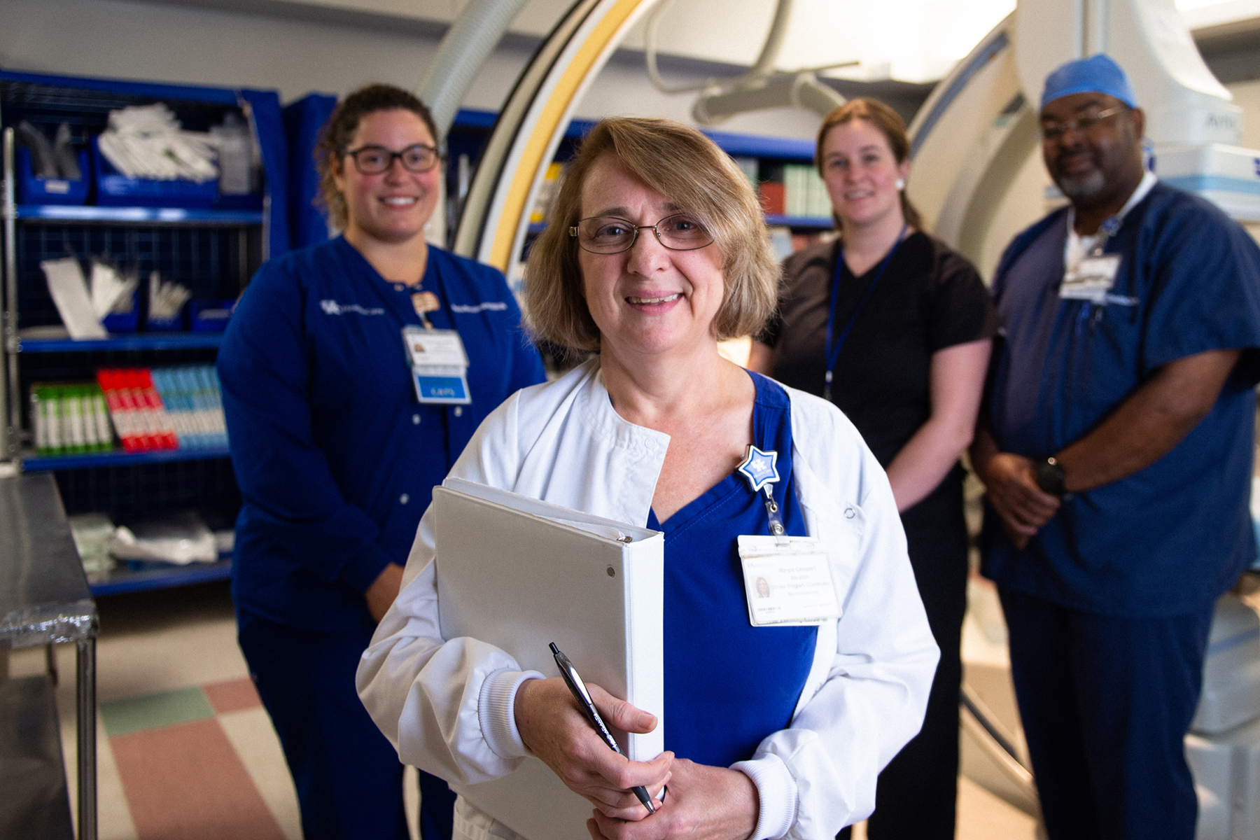 Margie Campbell holds a binder and smiles for a photo with other nurses at UK Healthcare.