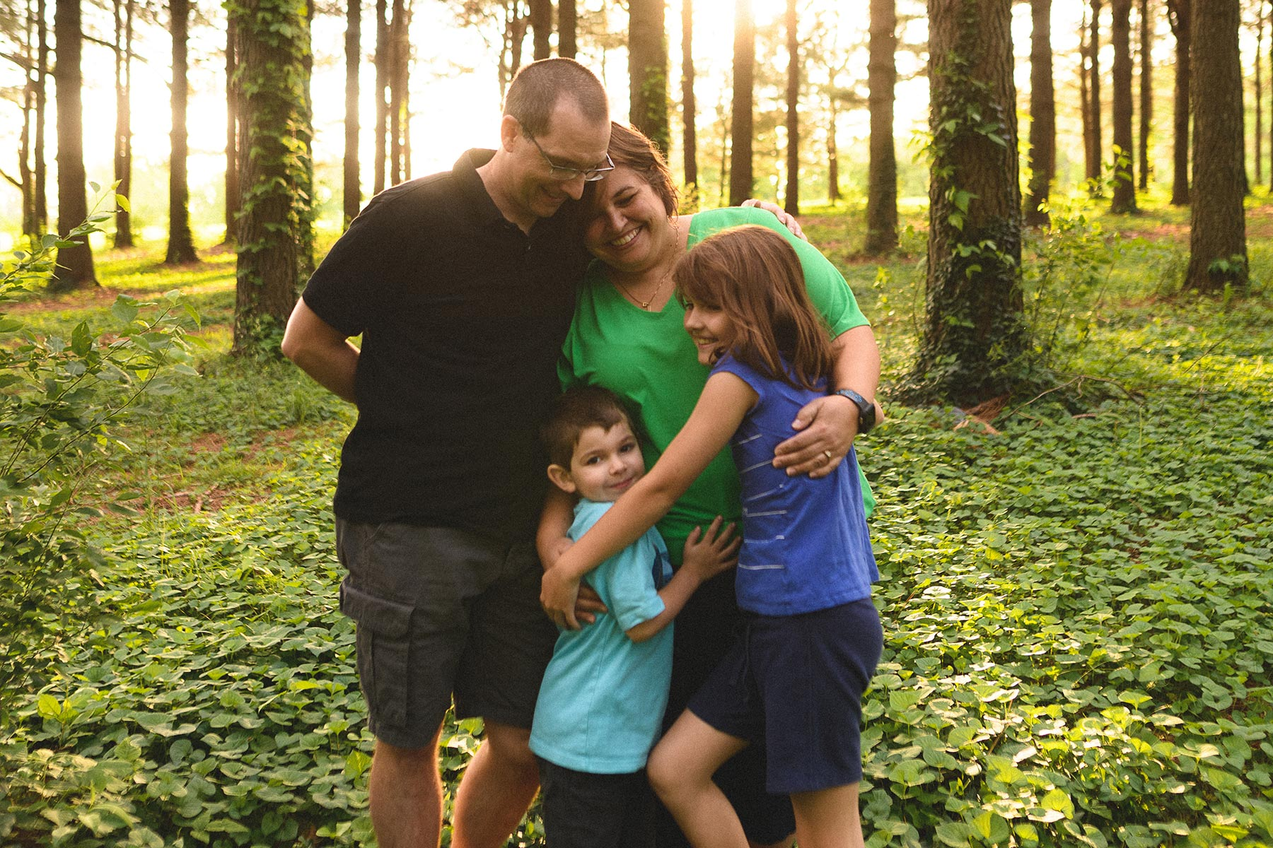 The Middleton family stops for a group hug and photo in a lush forest.
