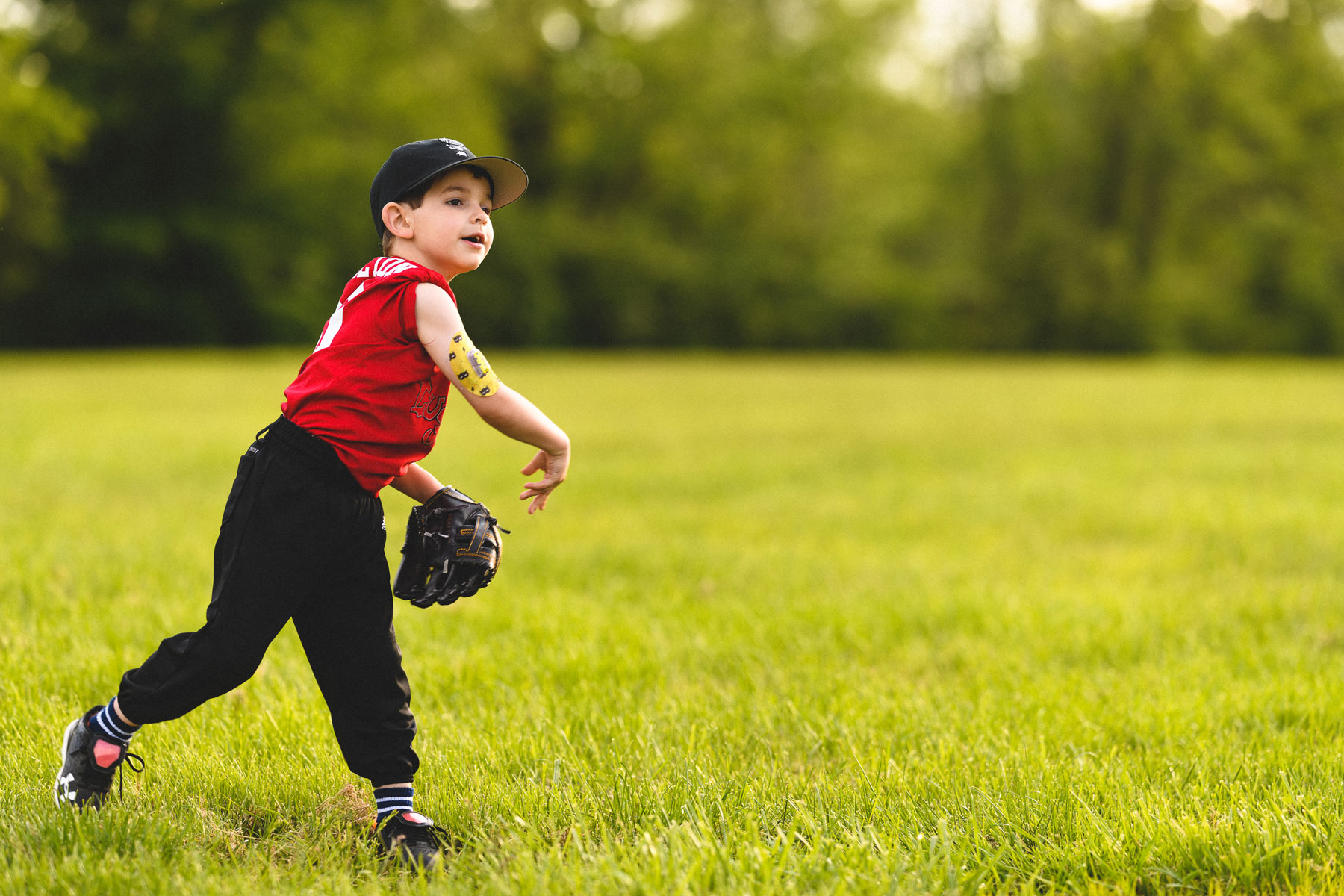 Max throws a baseball in his team uniform. His insulin pump is visible on the back of his upper arm.