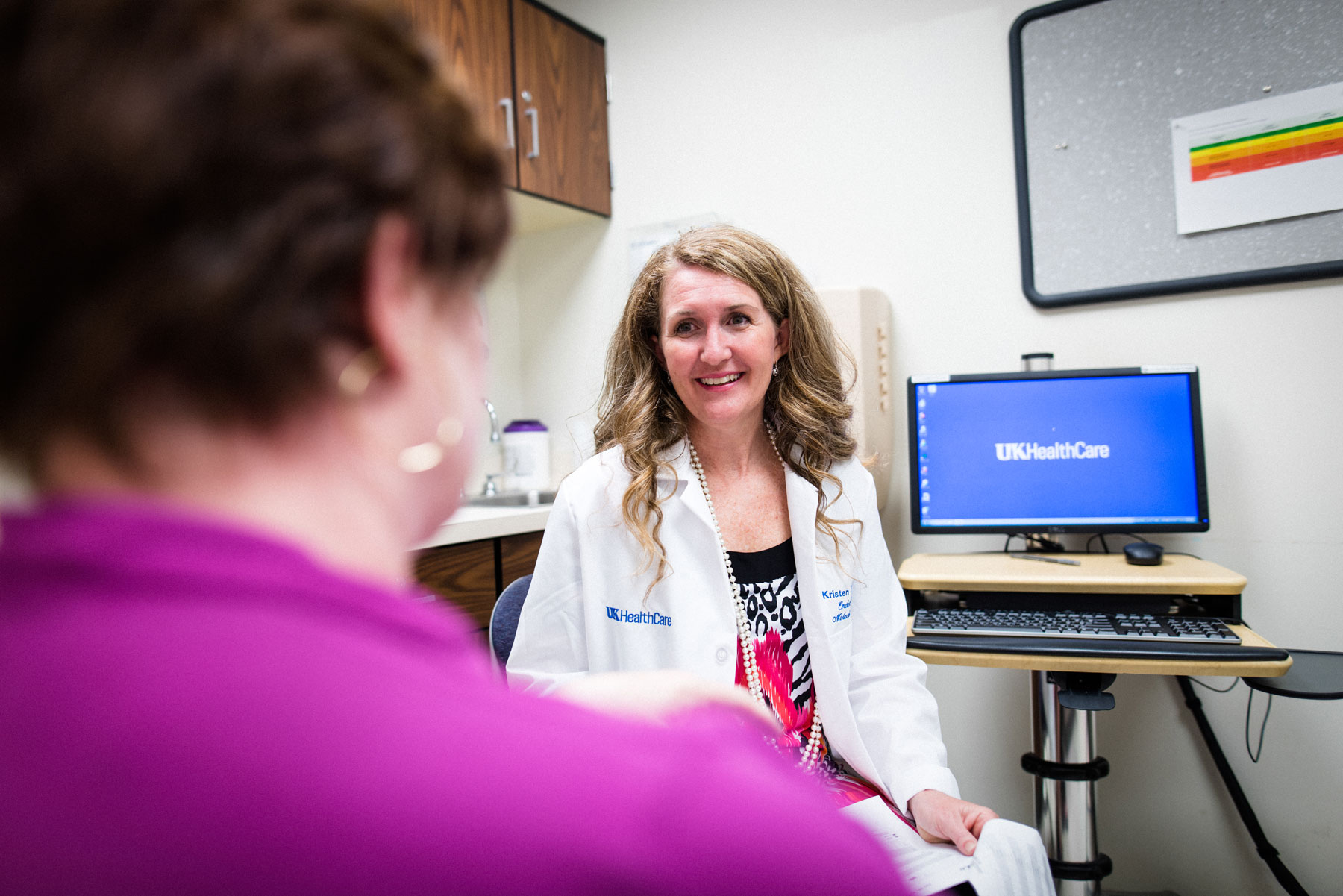 Dr. Kristen Stakelin talks to Teresa in an examination room.
