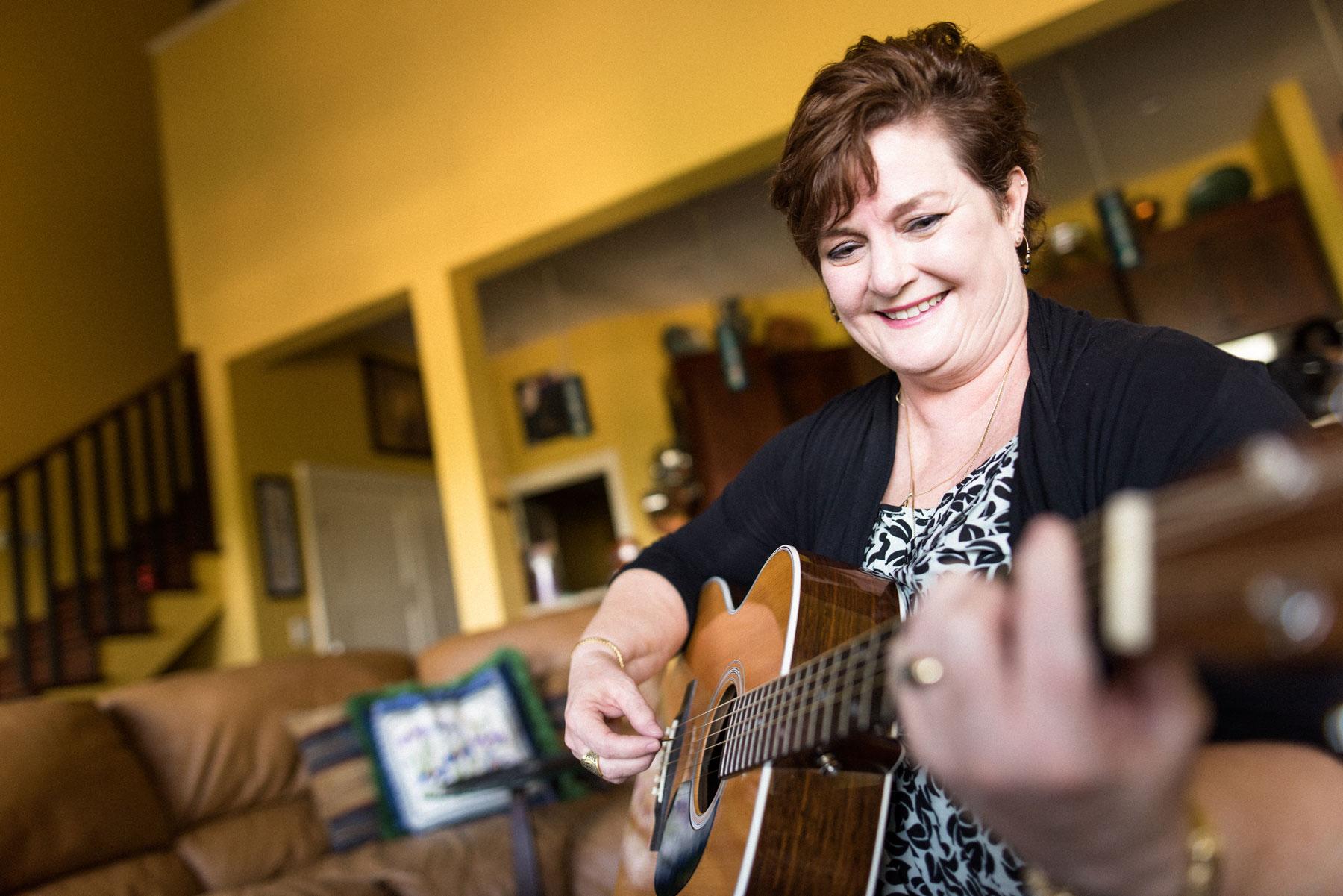 Teresa plays guitar in her living room.