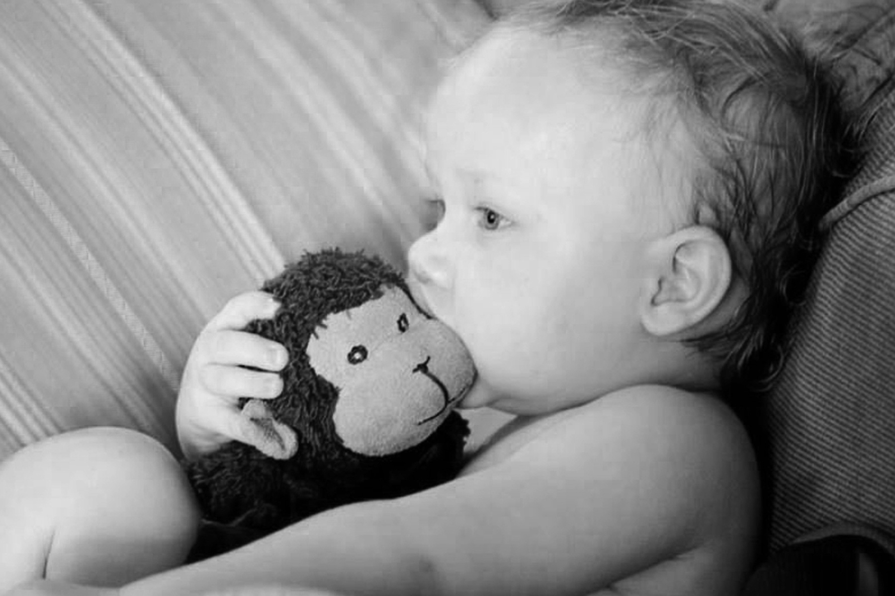 A black and white baby photo of Ezra with the original Stinky Monkey.