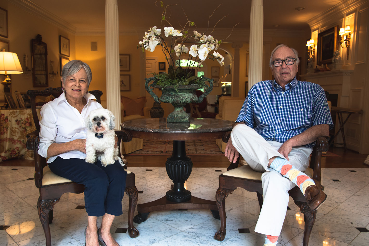 Gayle and her husband rest in chairs in their living room with their dog on Gayle's lap.