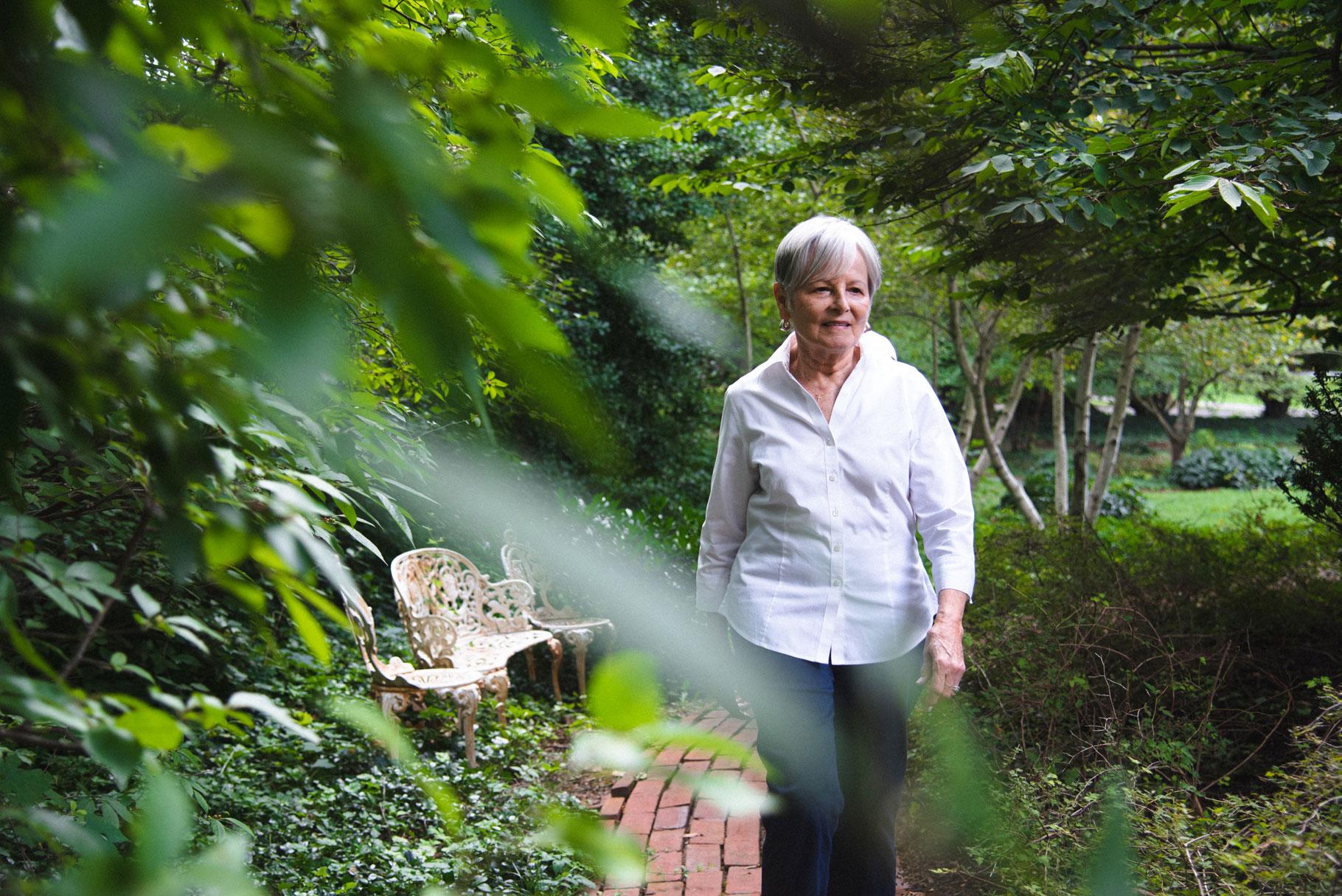 Gayle walks along a red brick path in her garden.