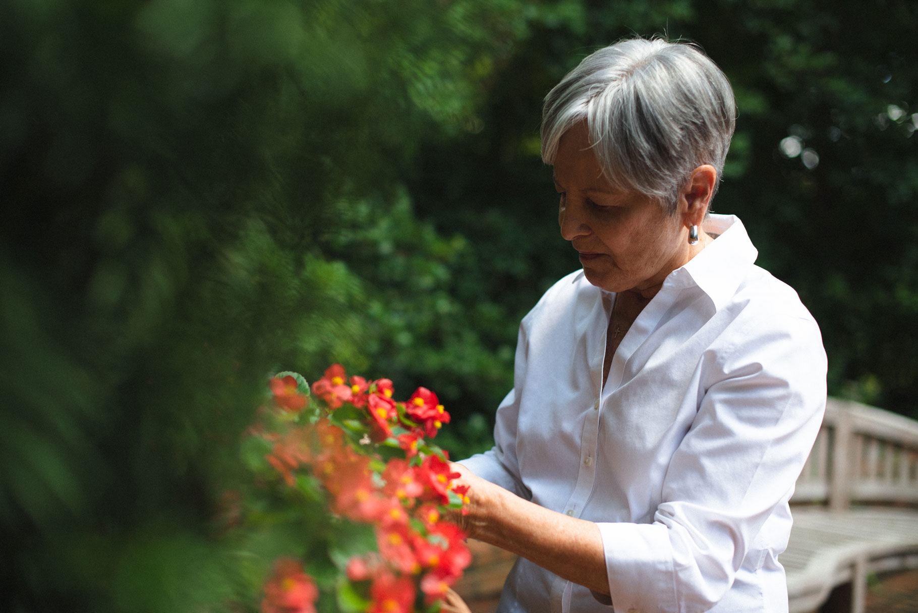 Gayle tends to a plant with red blossoms out in her garden.